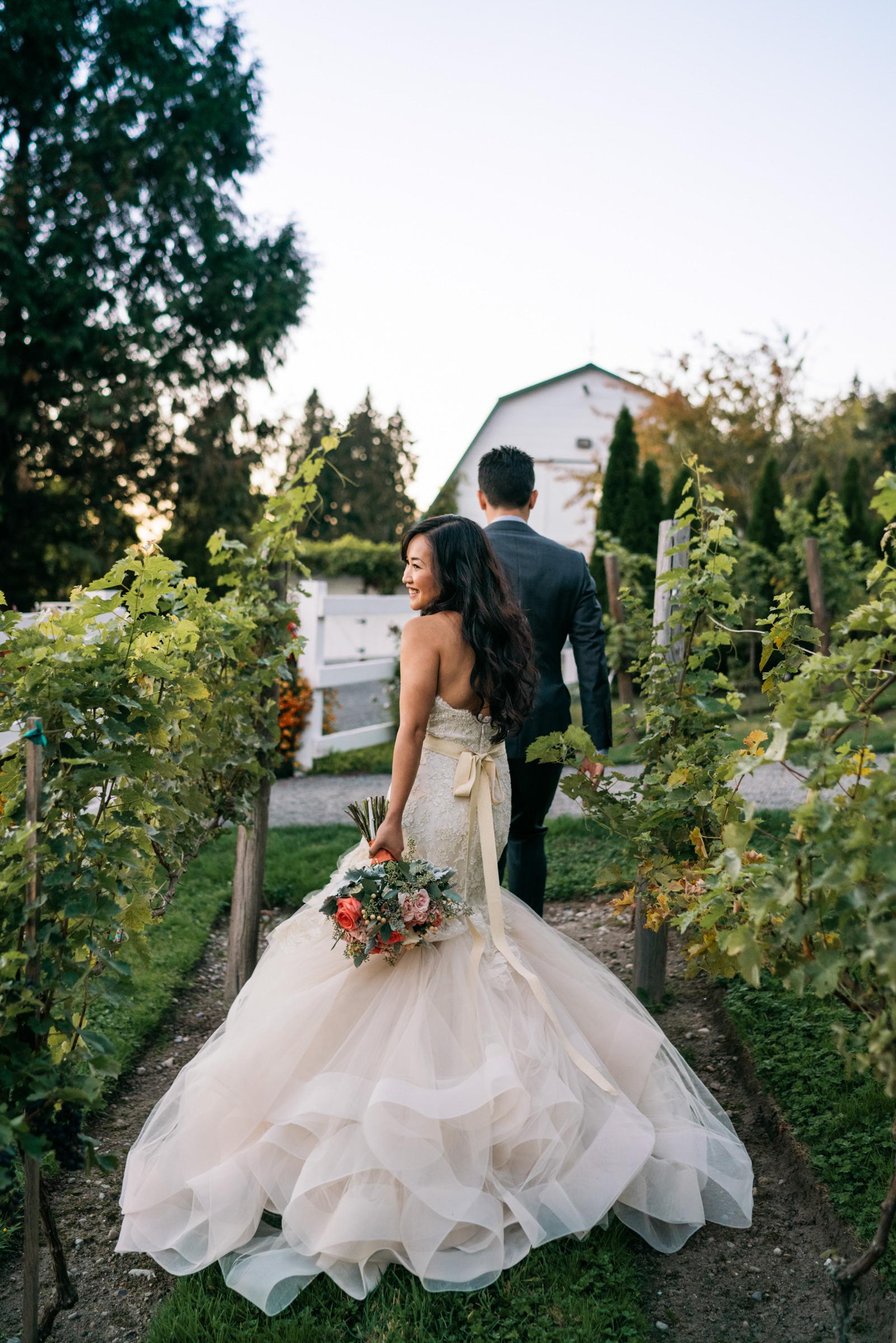 elegant-bride-in-trumpet-gown-with-groom-walk-in-grape-arbor-sasha-reiko-photography