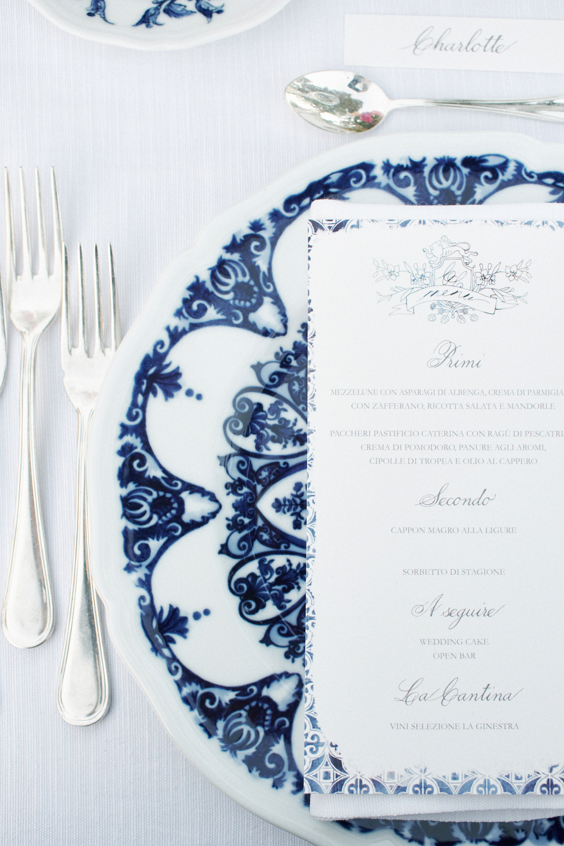 place-setting-with-silverware-menu-and-place-card-on-ornate-plate-andrea-bagnasco-fotografie
