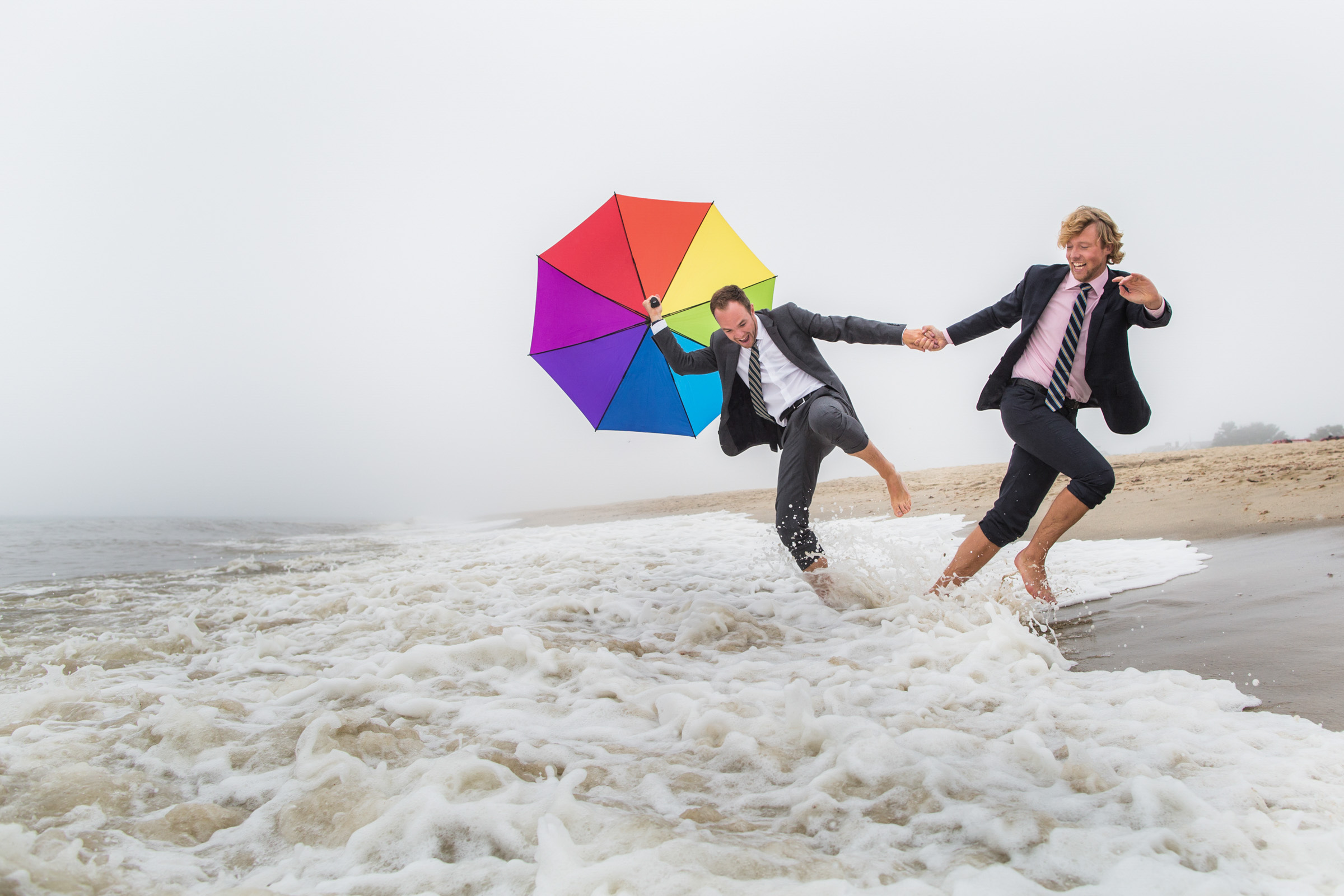 playful-grooms-at-surf-s-edge-with-rainbow-umbrella-katie-kaizer-photography