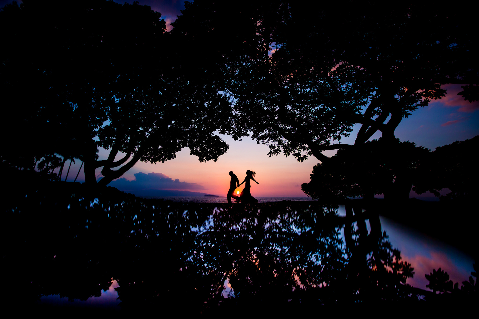 Beautiful sunset silhouette of wedding couple by Two Mann Studios