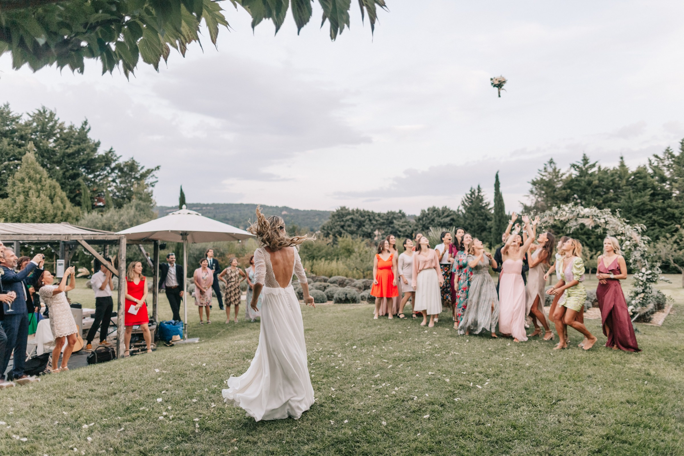 French bride in braids throwing her bouquet - photo by Amandine Ropars - wedding photographer in France