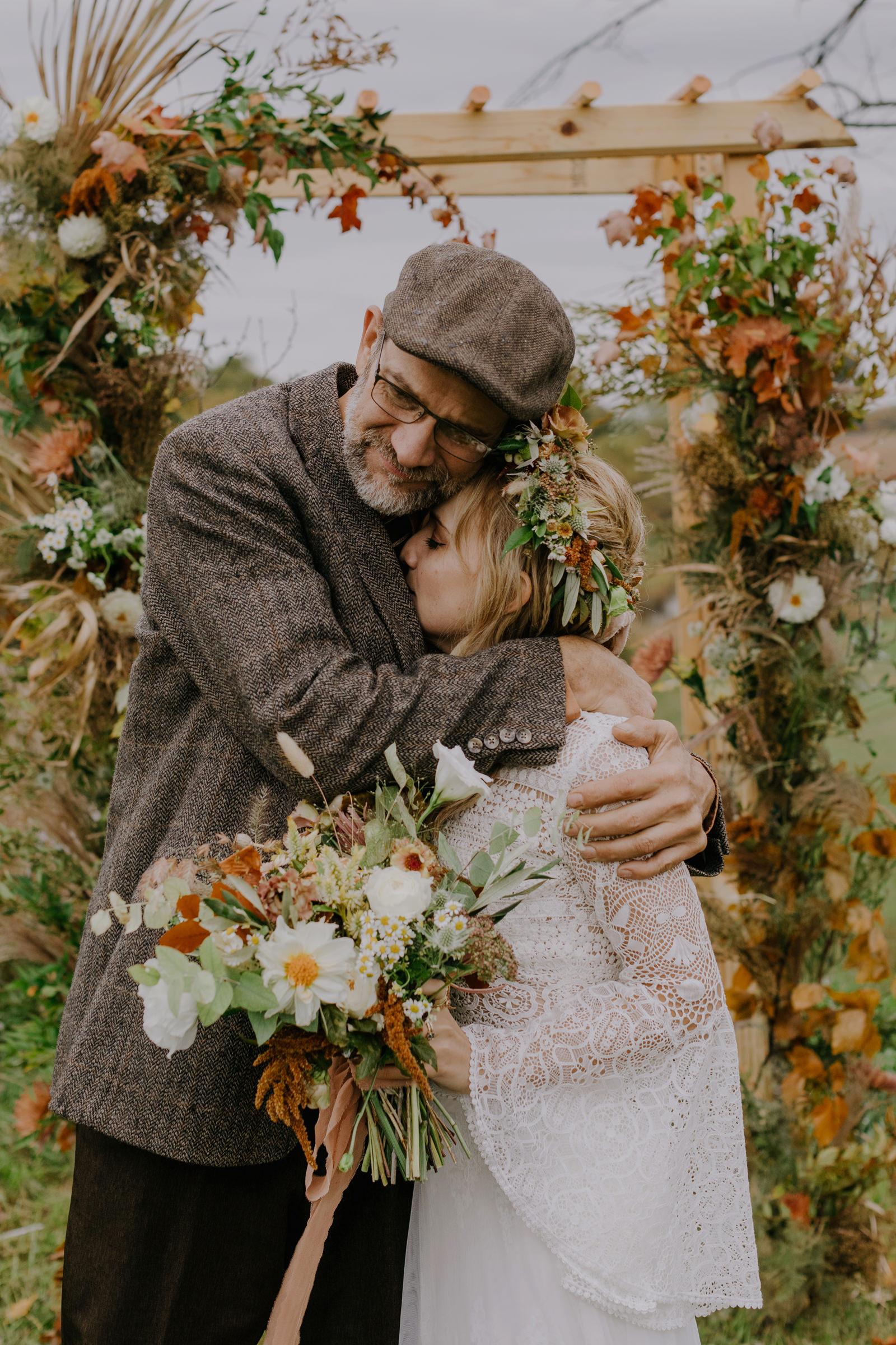 father-embraces-bride-against-floral-arbor-nirav-patel-photography