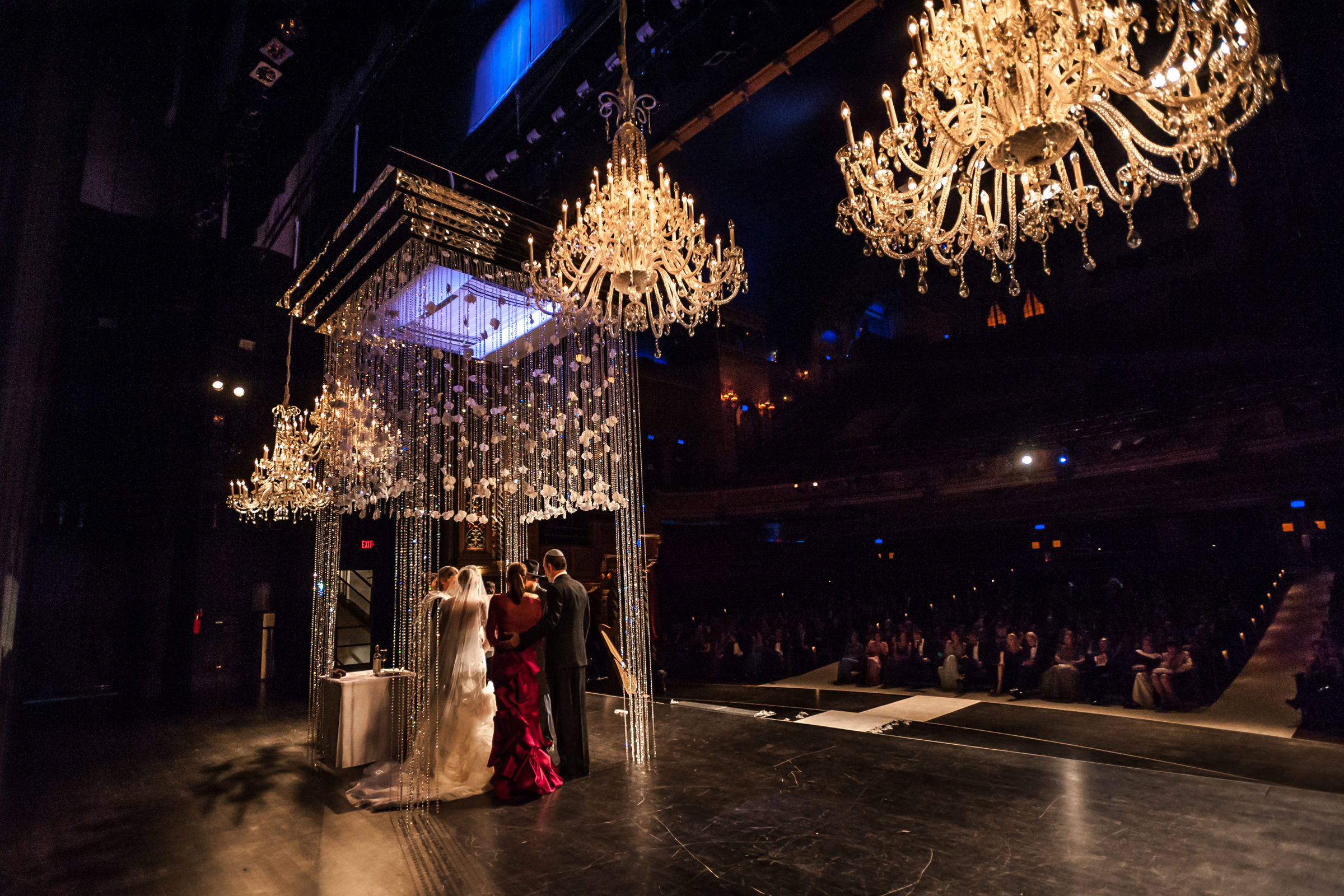 jewish-ceremony-under-elaborate-crystal-huppah-with-chandeliers-in-theatre.jpg