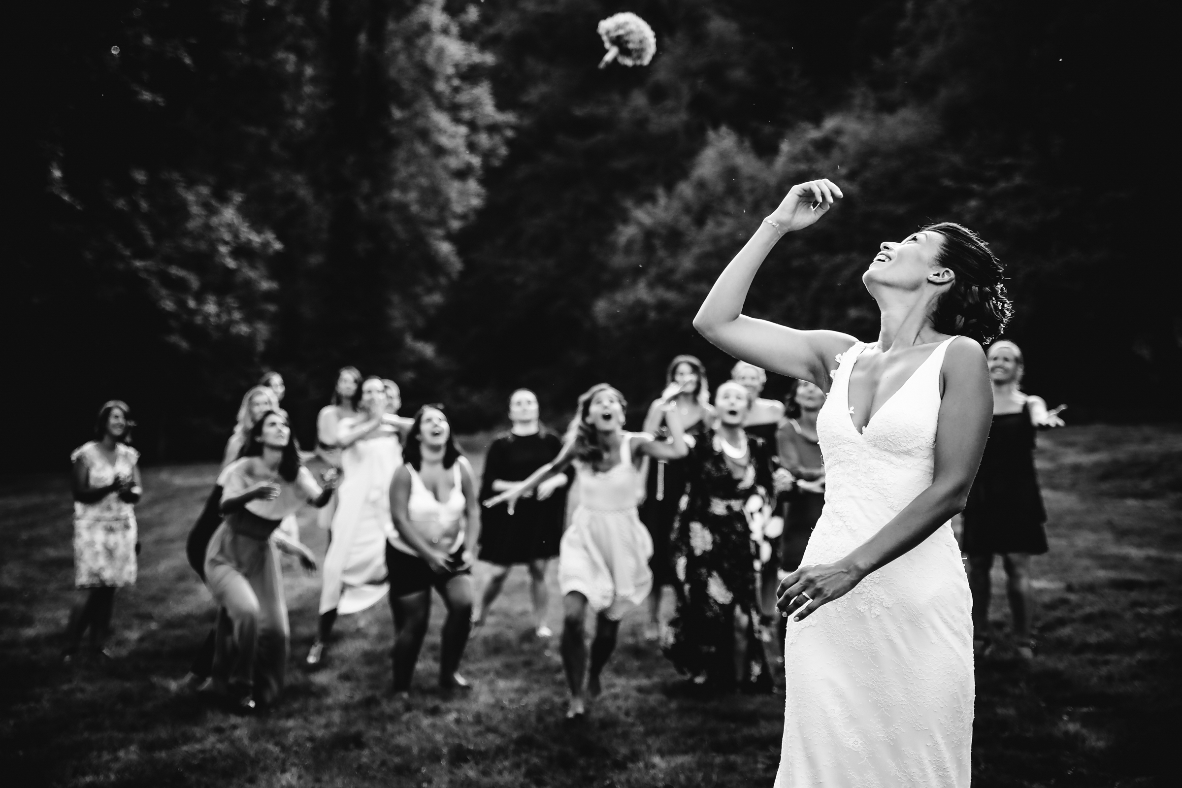 Bride looks over her shoulder while she throws her bouquet - photo by Julien Laurent Georges - wedding photographer in France