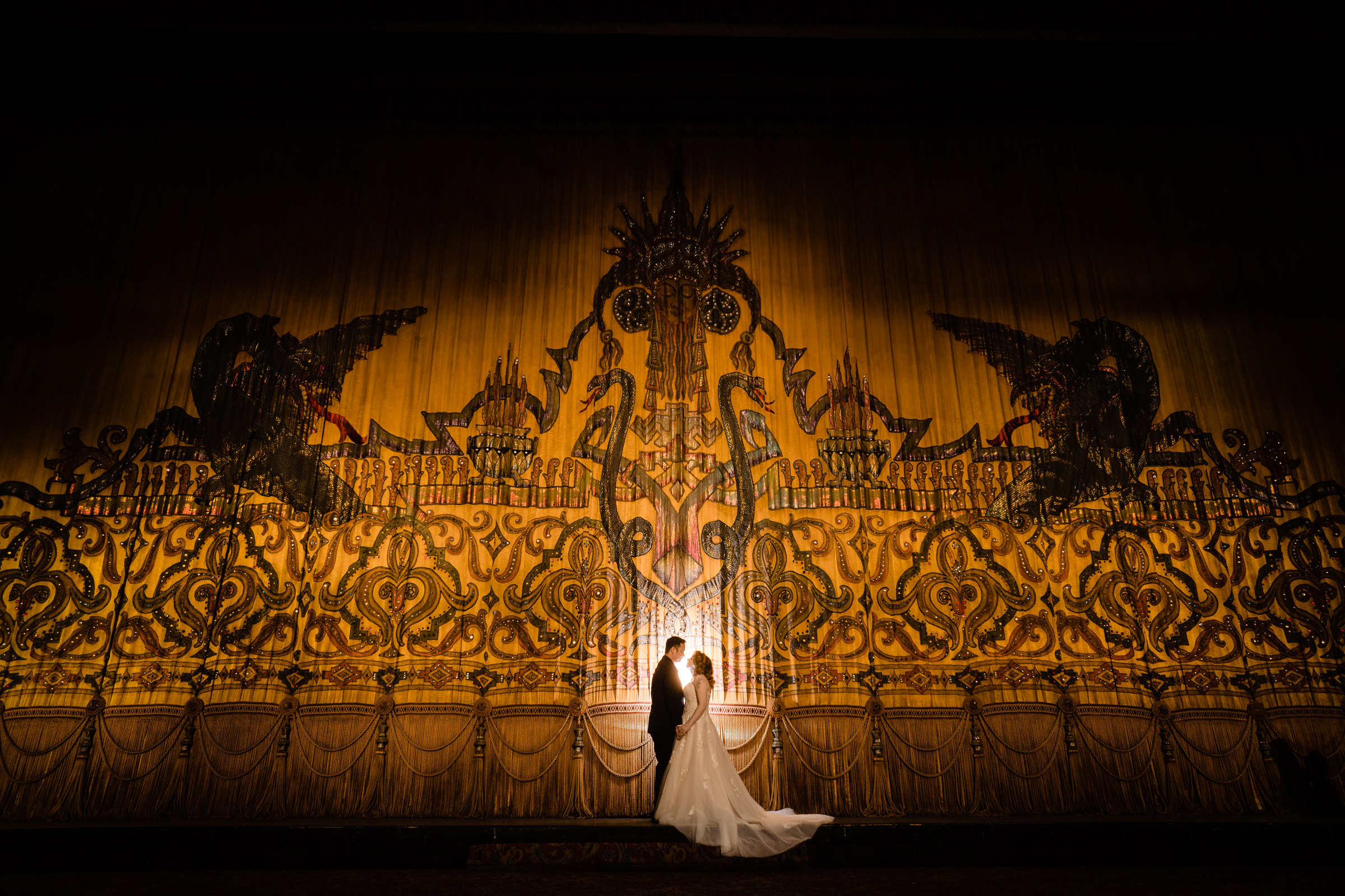 couple-in-spotlight-against-theater-curtain-vinson-images