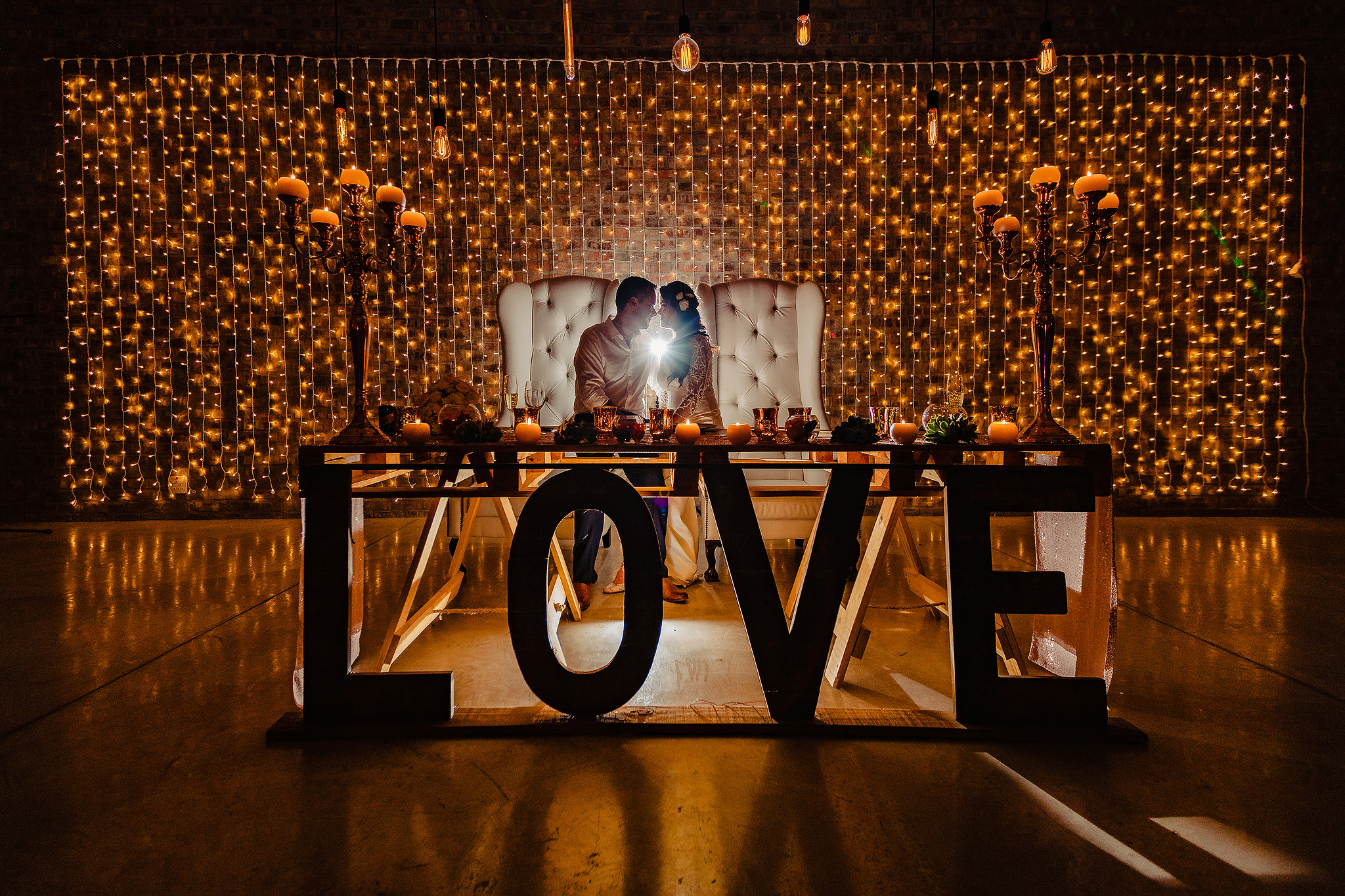 couple-seated-against-lights-and-huge-love-sign-ruan-redelinghuys-photography