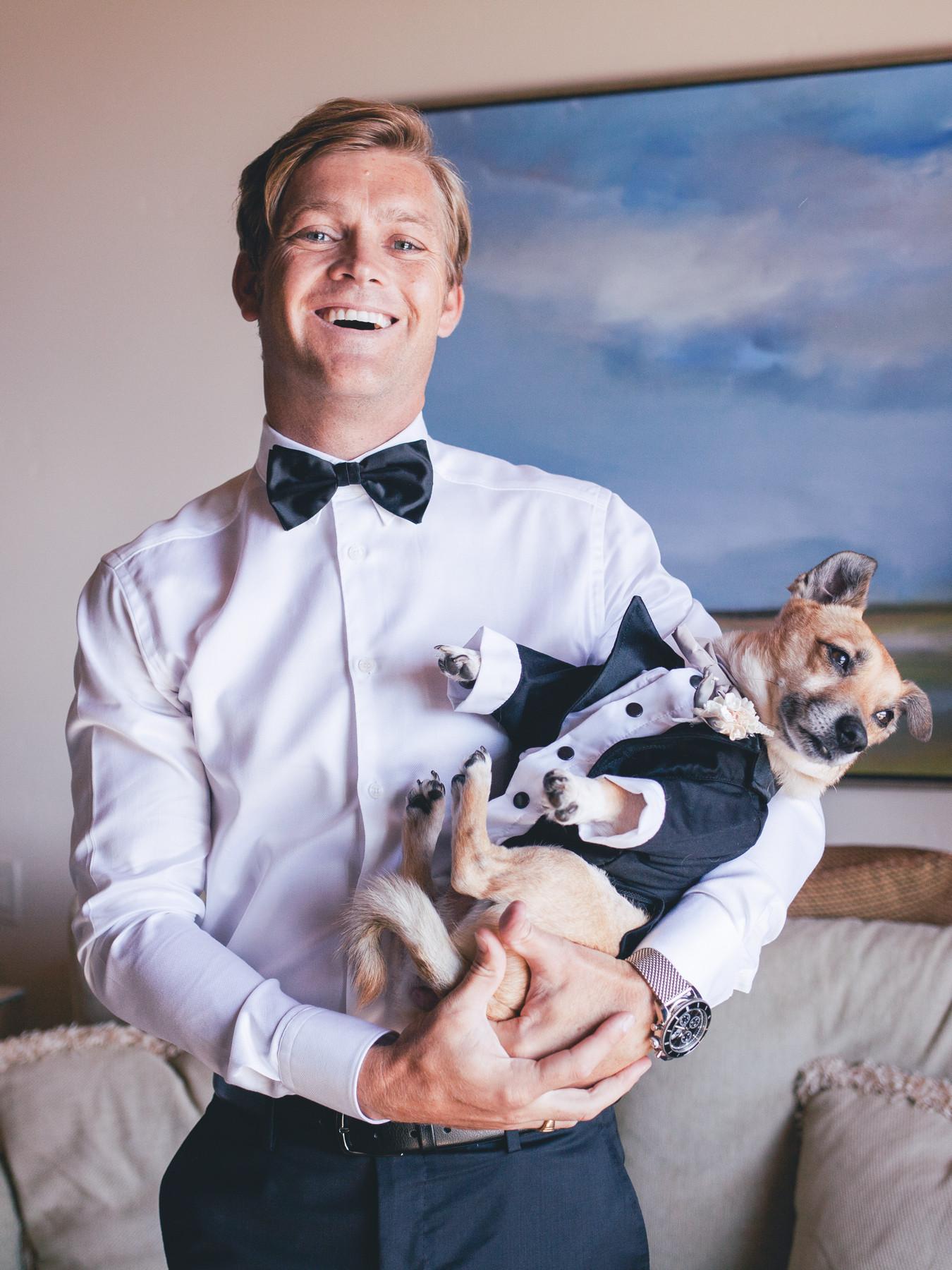Happy groom with tuxedoed dog - photo by John and Joseph