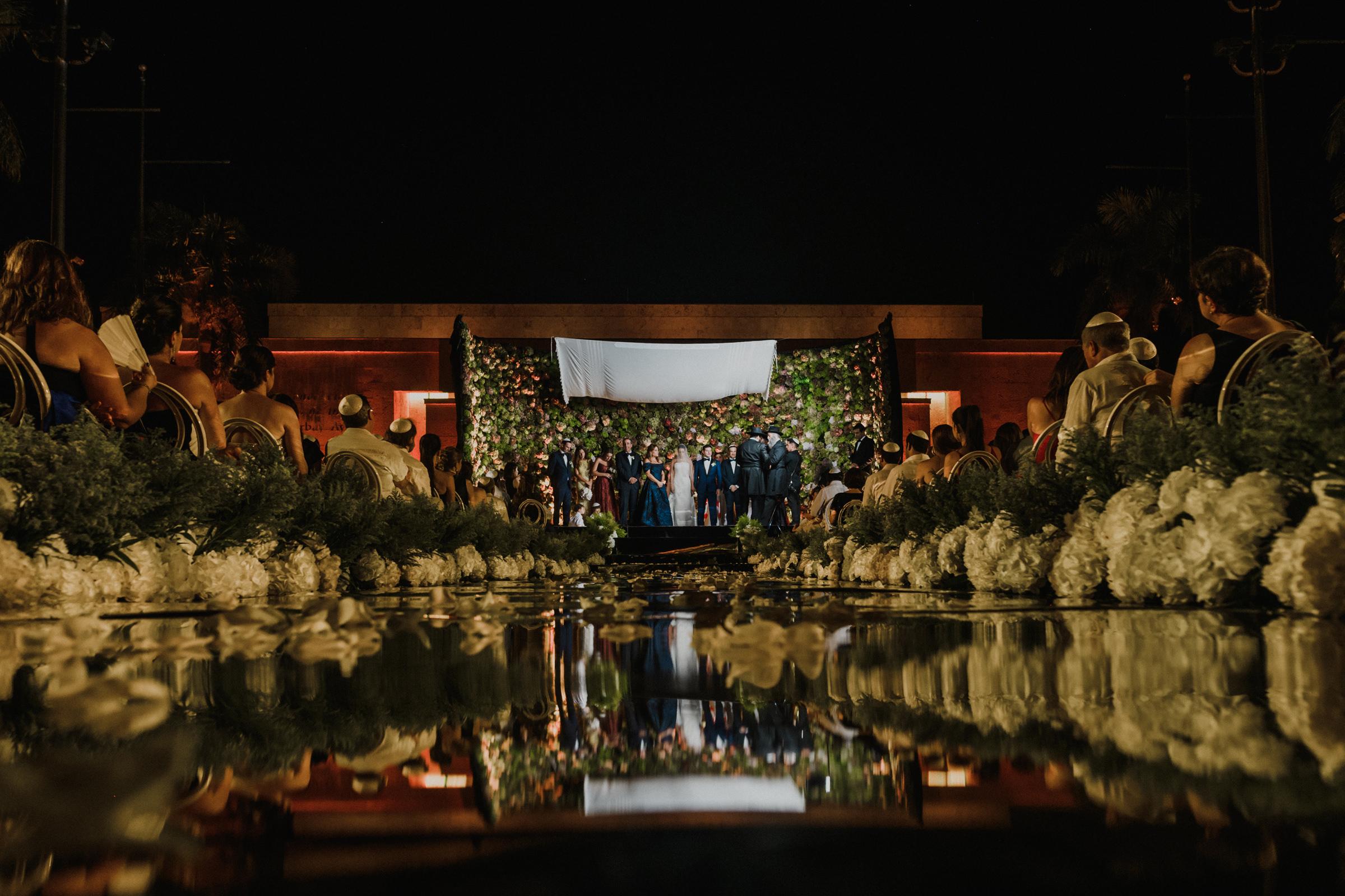 elaborate-floral-wall-ceremony-reflected-in-pool-elmarcorojo-spain.jpg