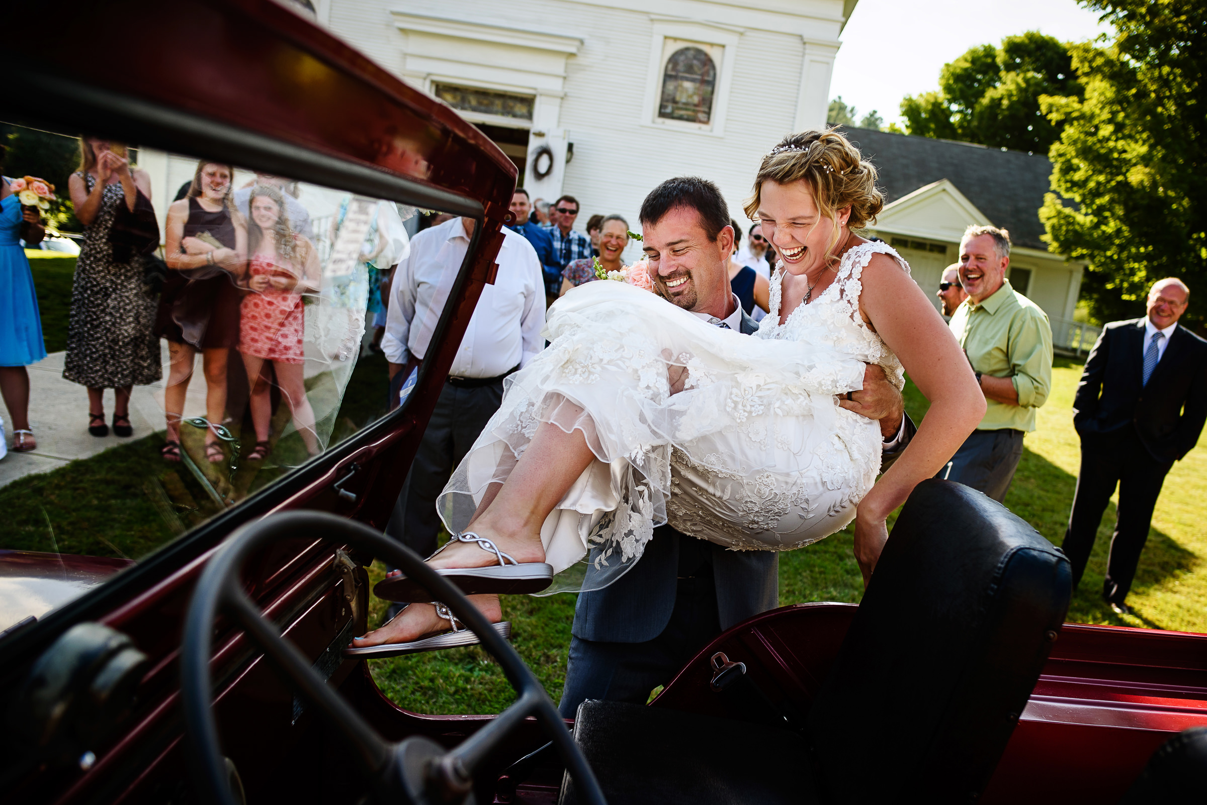 groom-picking-up-bride-happily-to-drop-her-into-the-getaway-car-after-ceremony-photo-by-hannah-photography
