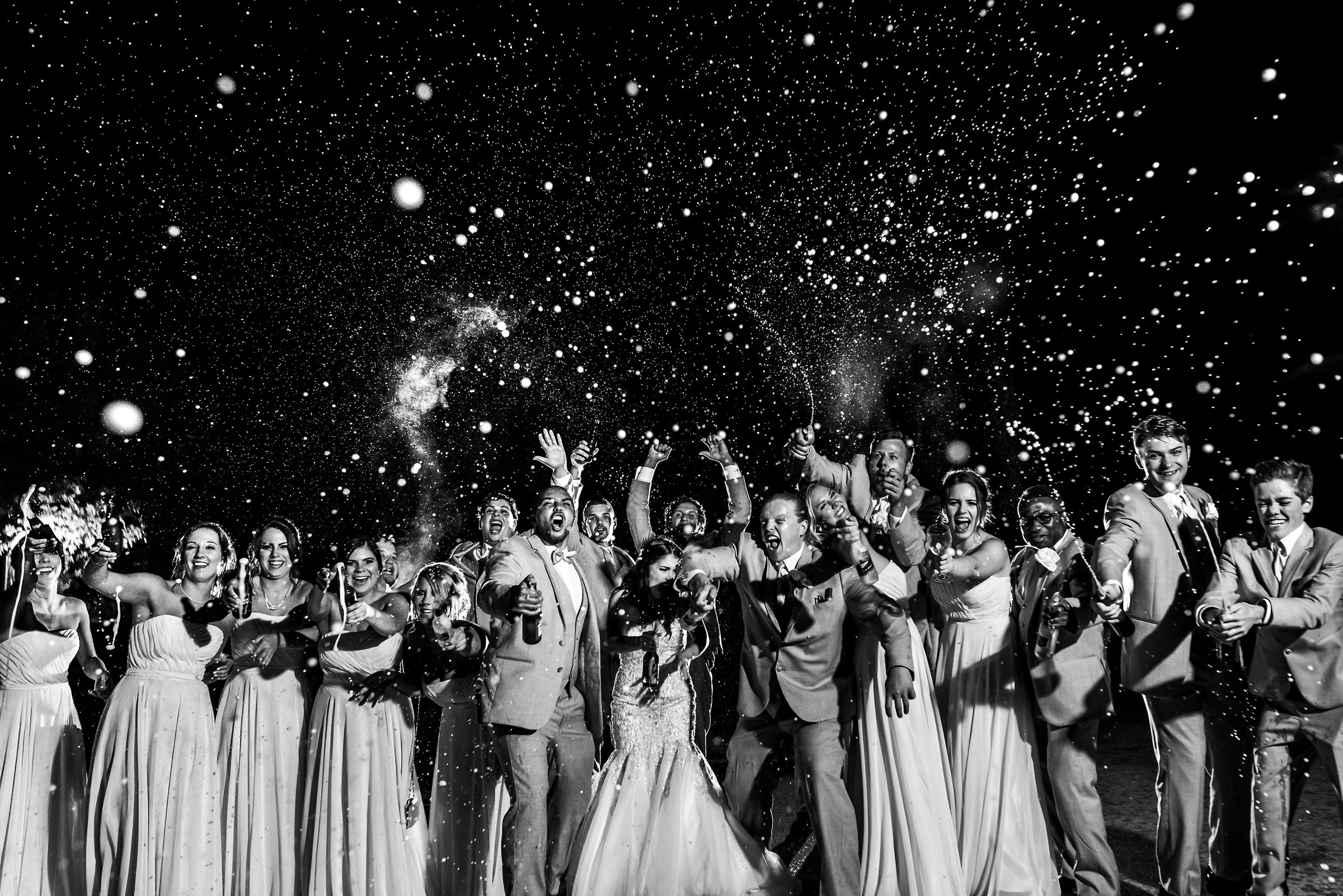 group-shot-of-bridal-party-popping-champagne-moore-photography