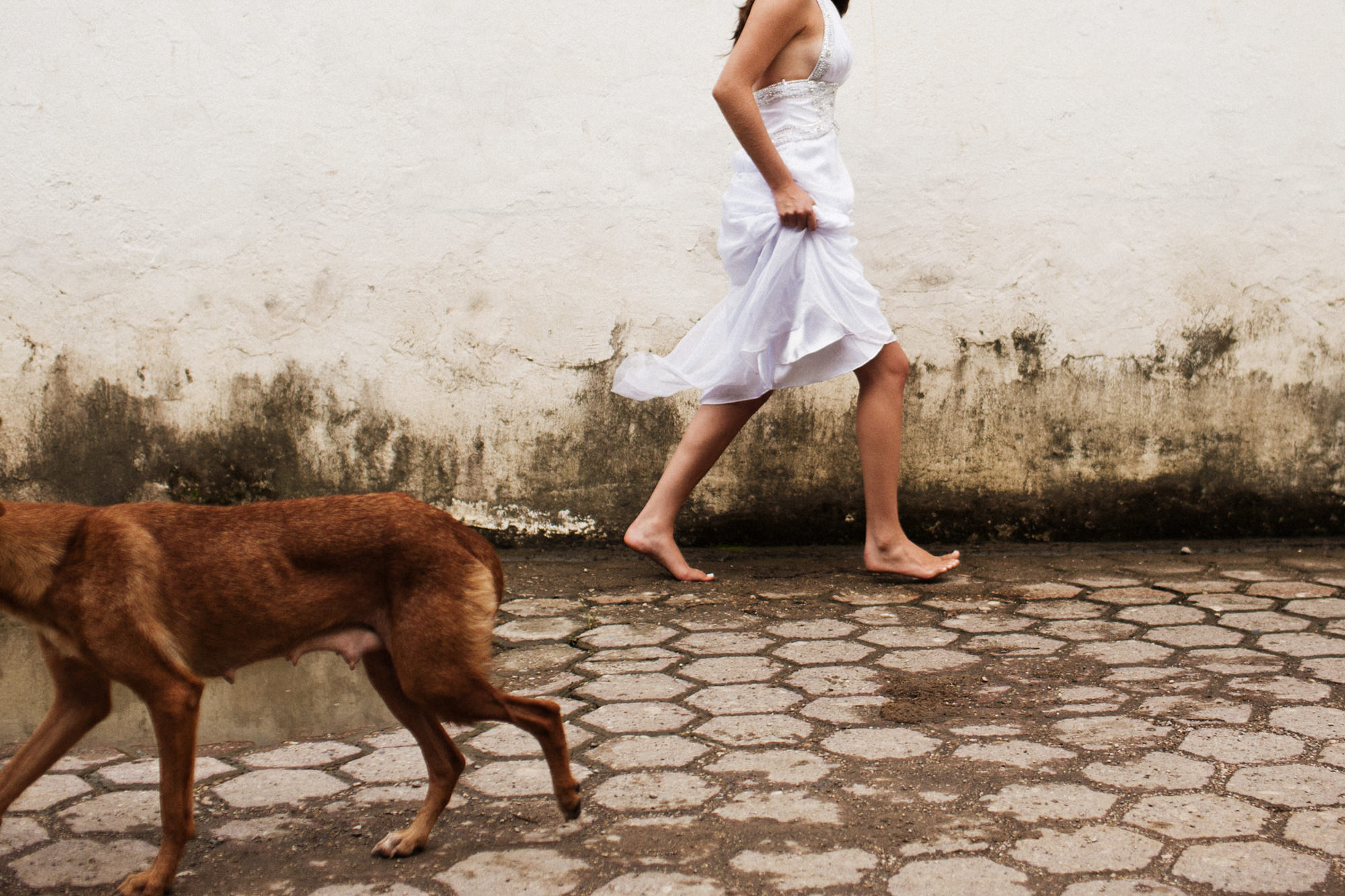 Bride walking barefoot down cobblestone street - photo by Fer Juaristi - Mexico