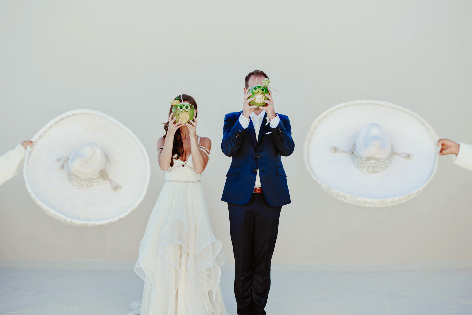 Portrait of bride and groom with coconuts in front of their faces by Fer Juaristi - Mexico
