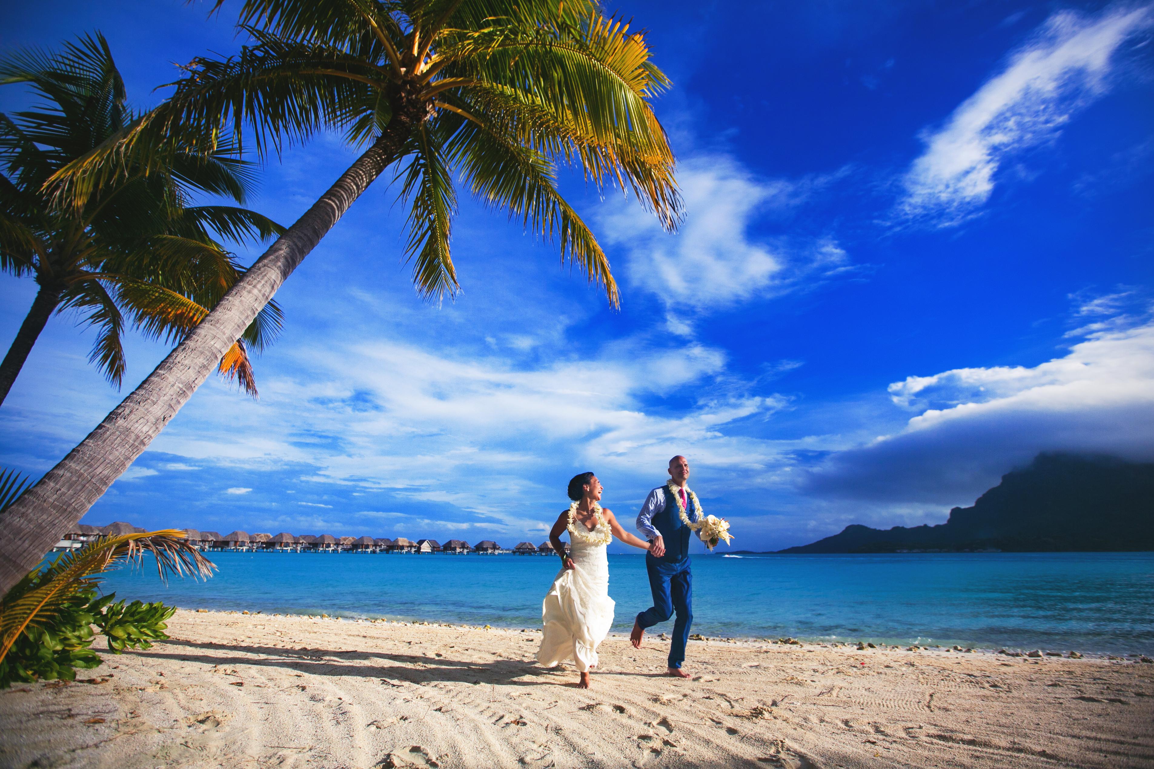 Couple running on beach near the Four Seasons Bora Bora, photo by Callaway Gable