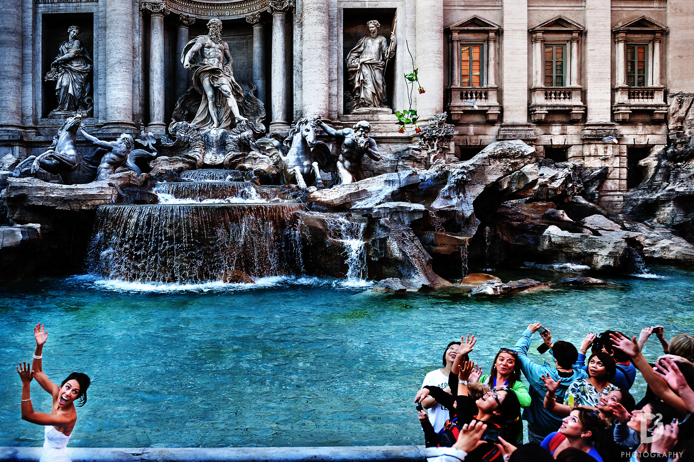 Bride throwing her bouquet to the crowd at the Trevi Fountain - D2 Photography