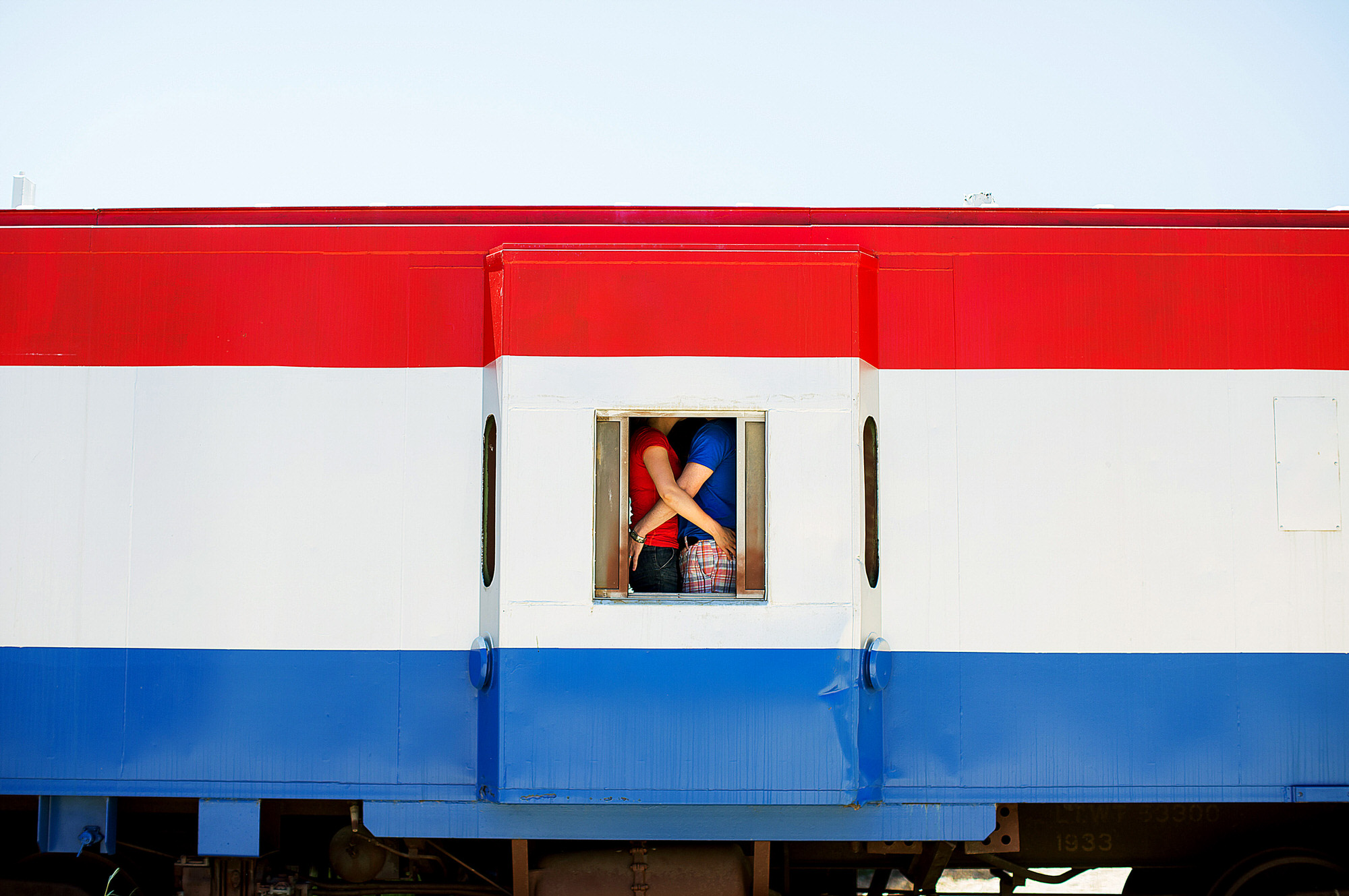 Couple embrace in red, white and blue train window - photo by Ken Pak - Washington, DC