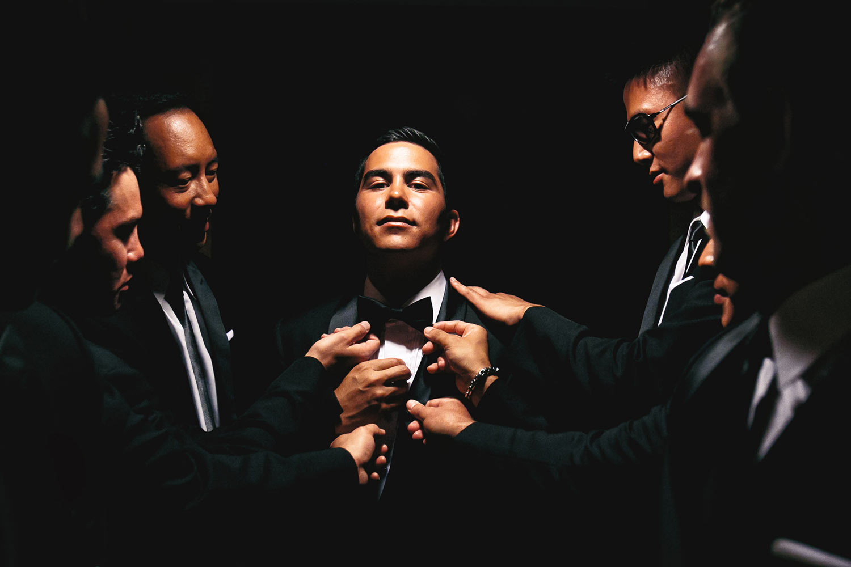 Dramatic photo of groomsmen adjust groom's tie - photo by Callaway Gable