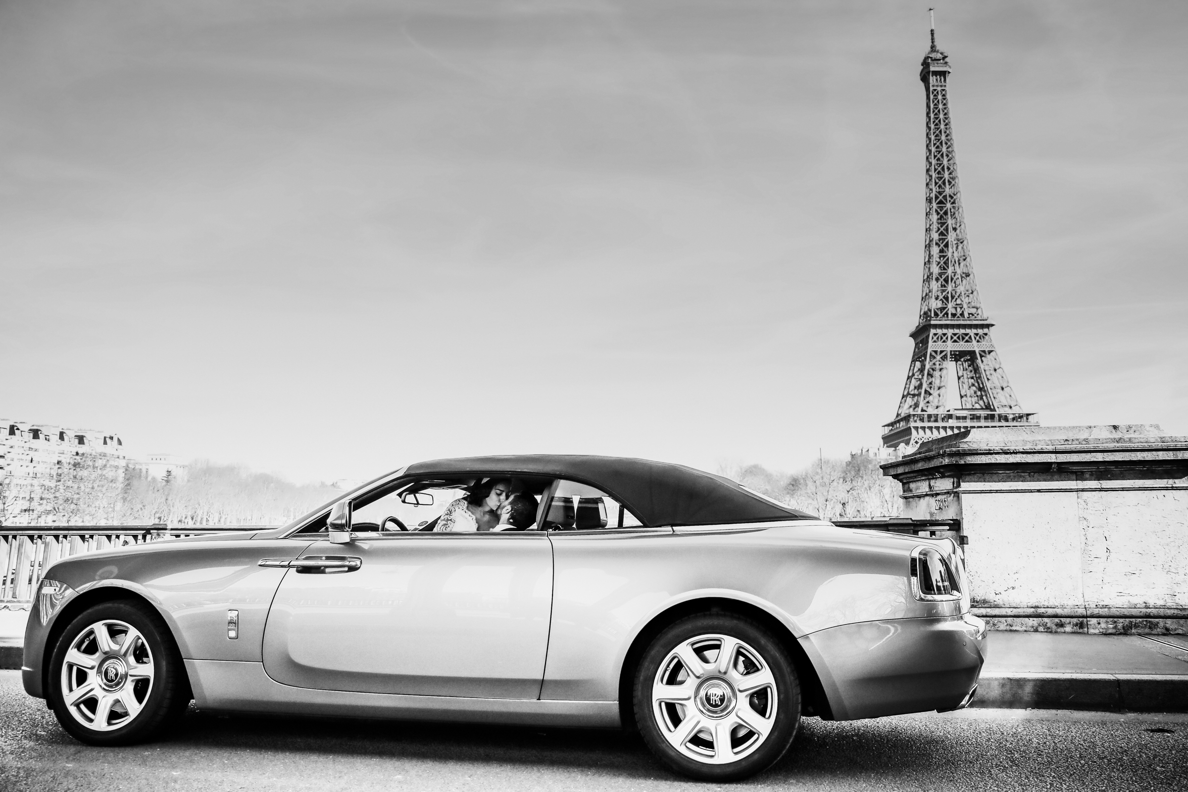 Couple kissing in car by the Eiffel Tower - photo by Julien Laurent Georges