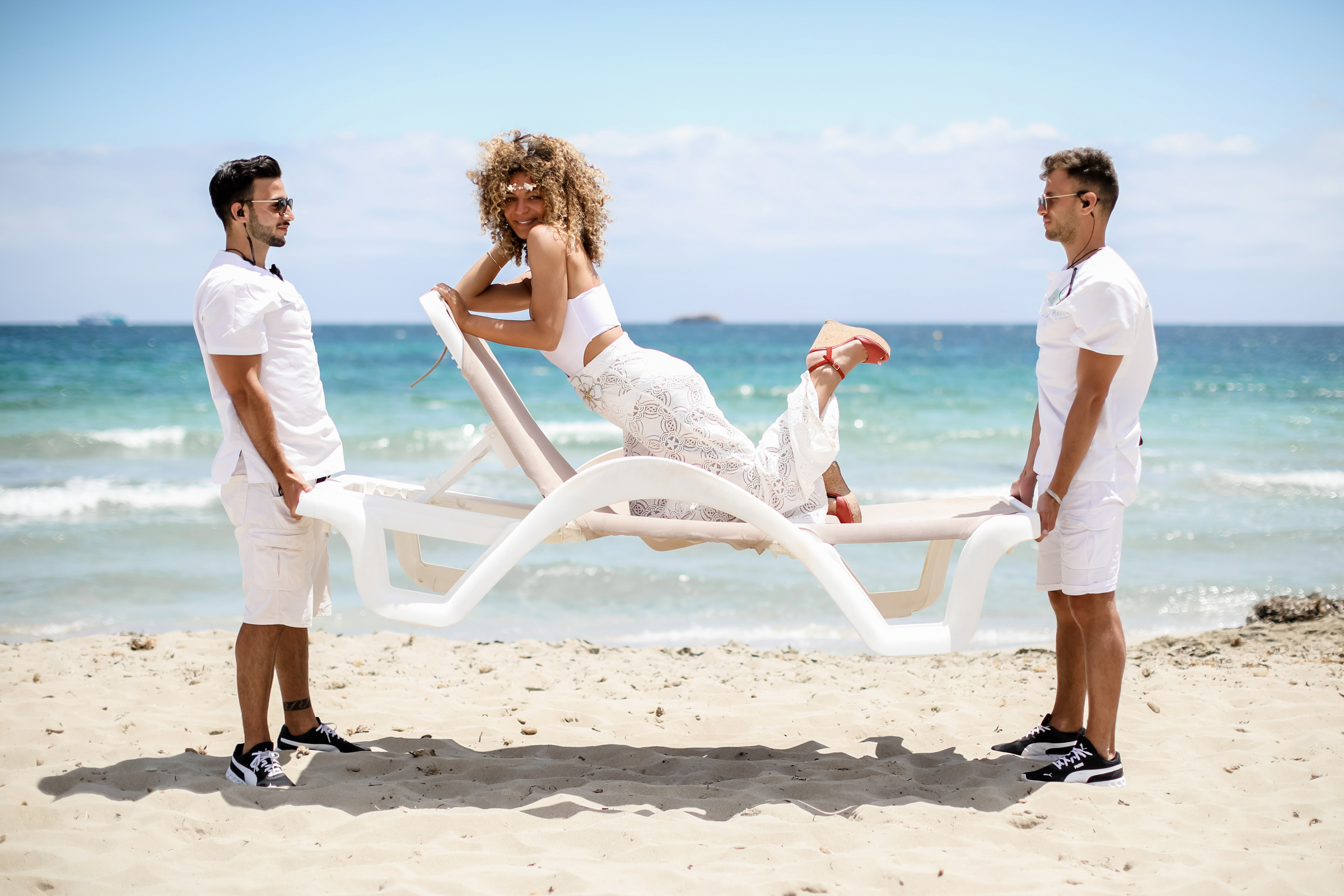 Bride posing on beach chair on Ibiza beach - photo by Julien Laurent Georges