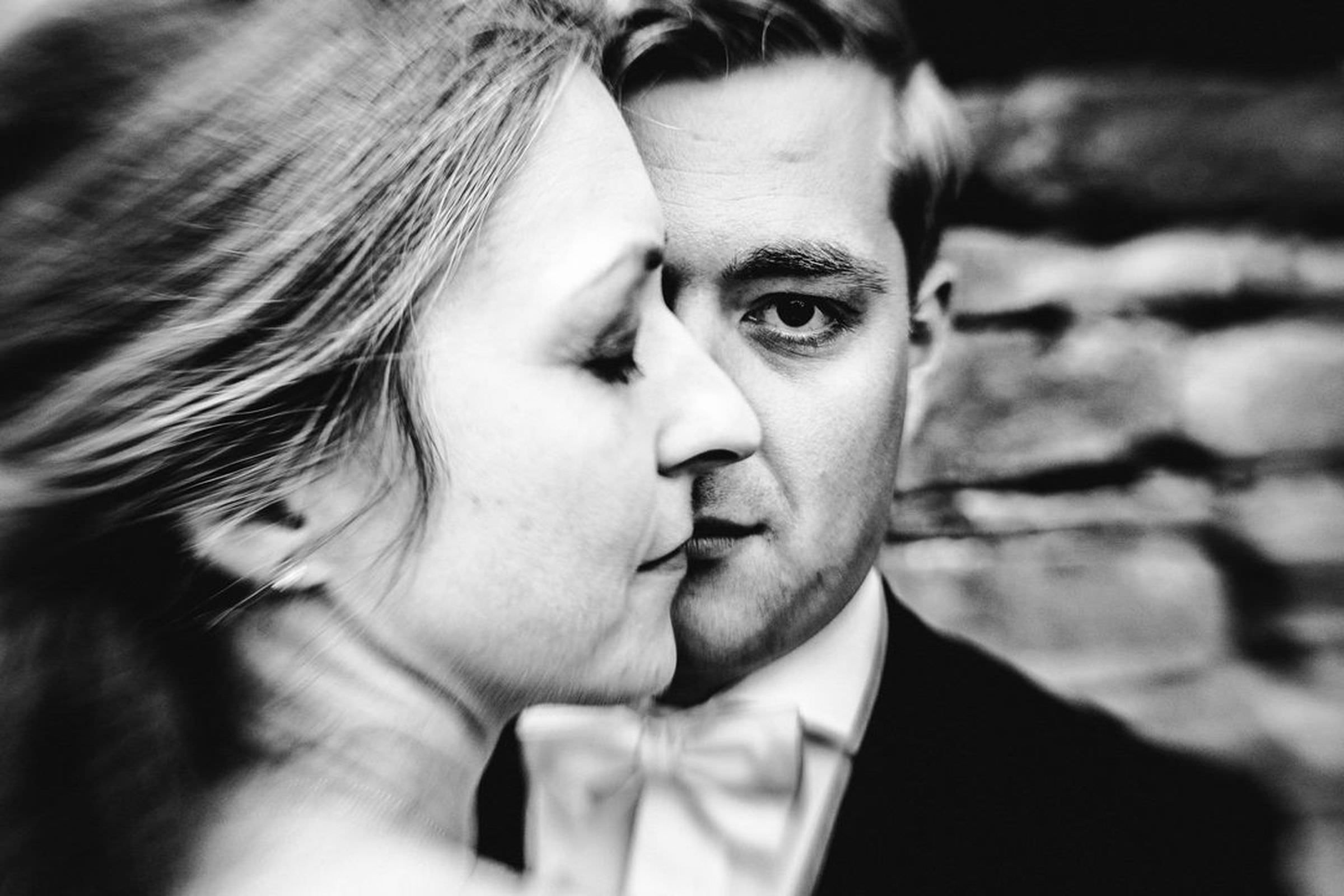 Black and white photo of groom with bride in foreground by FineArt Weddings Photography from Germany