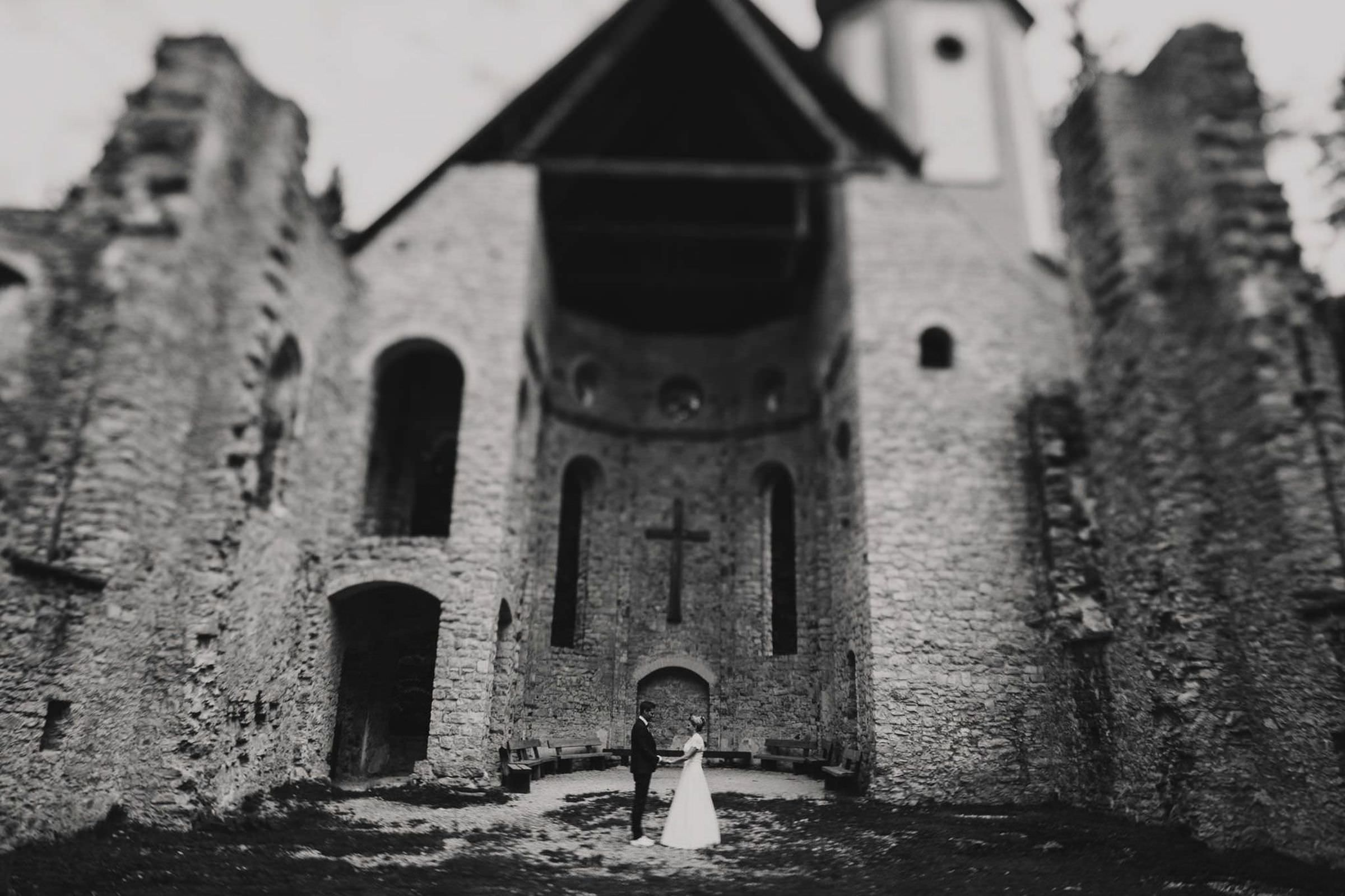 Black and white of couple in front of old church by FineArt Weddings Photography from Germany
