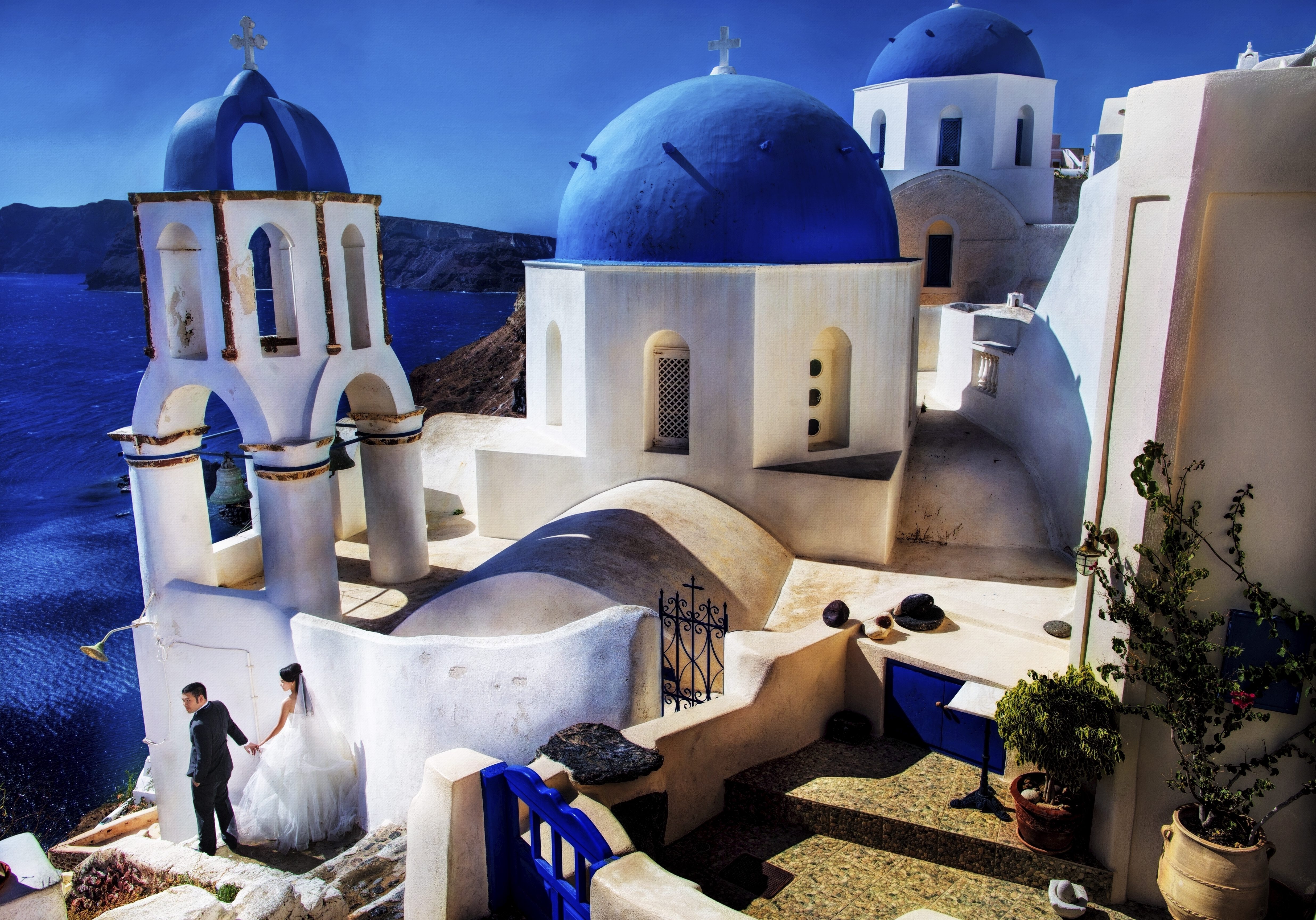 Couple holding hands against the white architecture of Santorini, Greece - photo by Edwin Tan