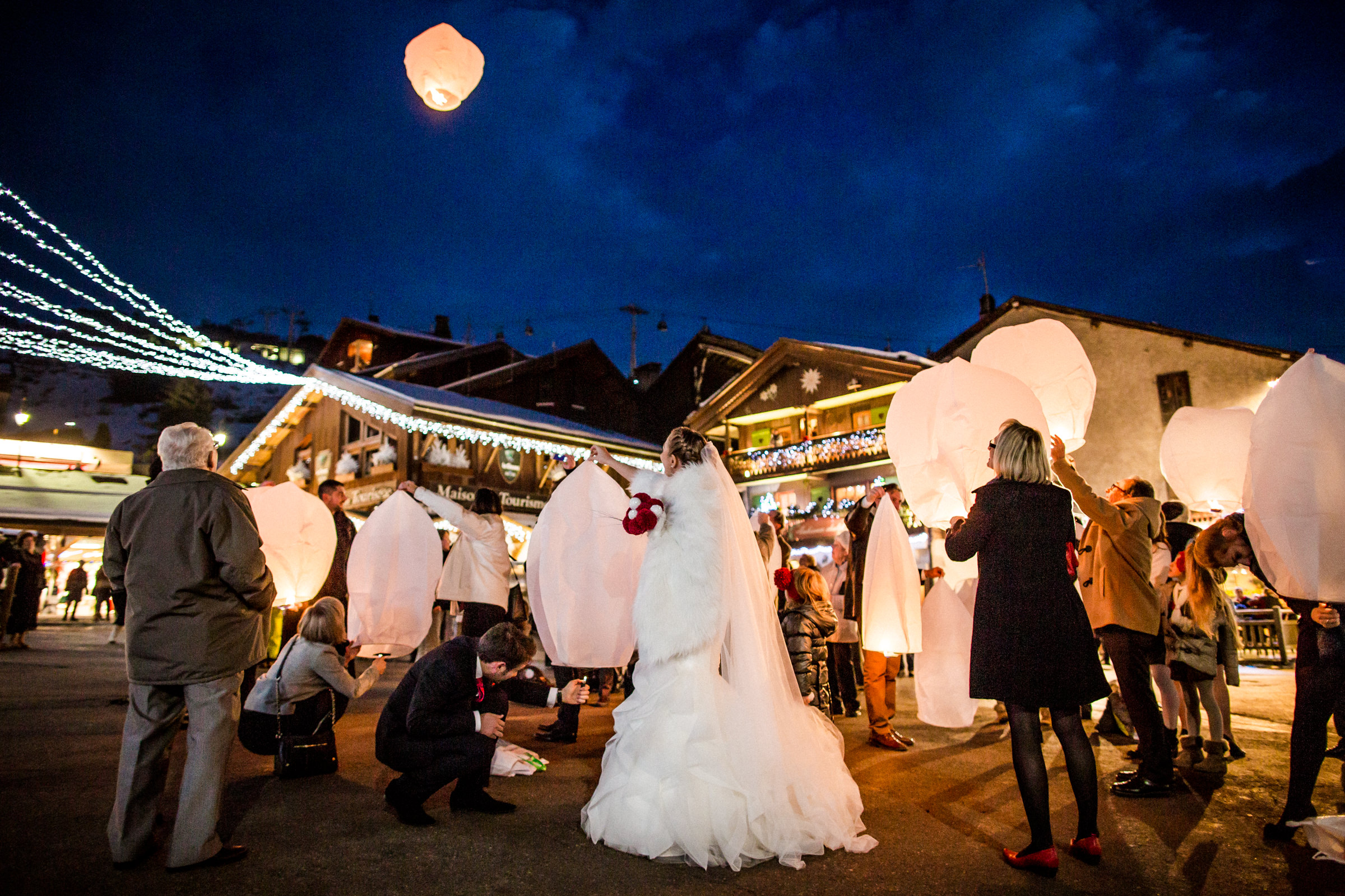 Lighting lanterns for marriage celebration in the French Alps - photo by William Lambelet