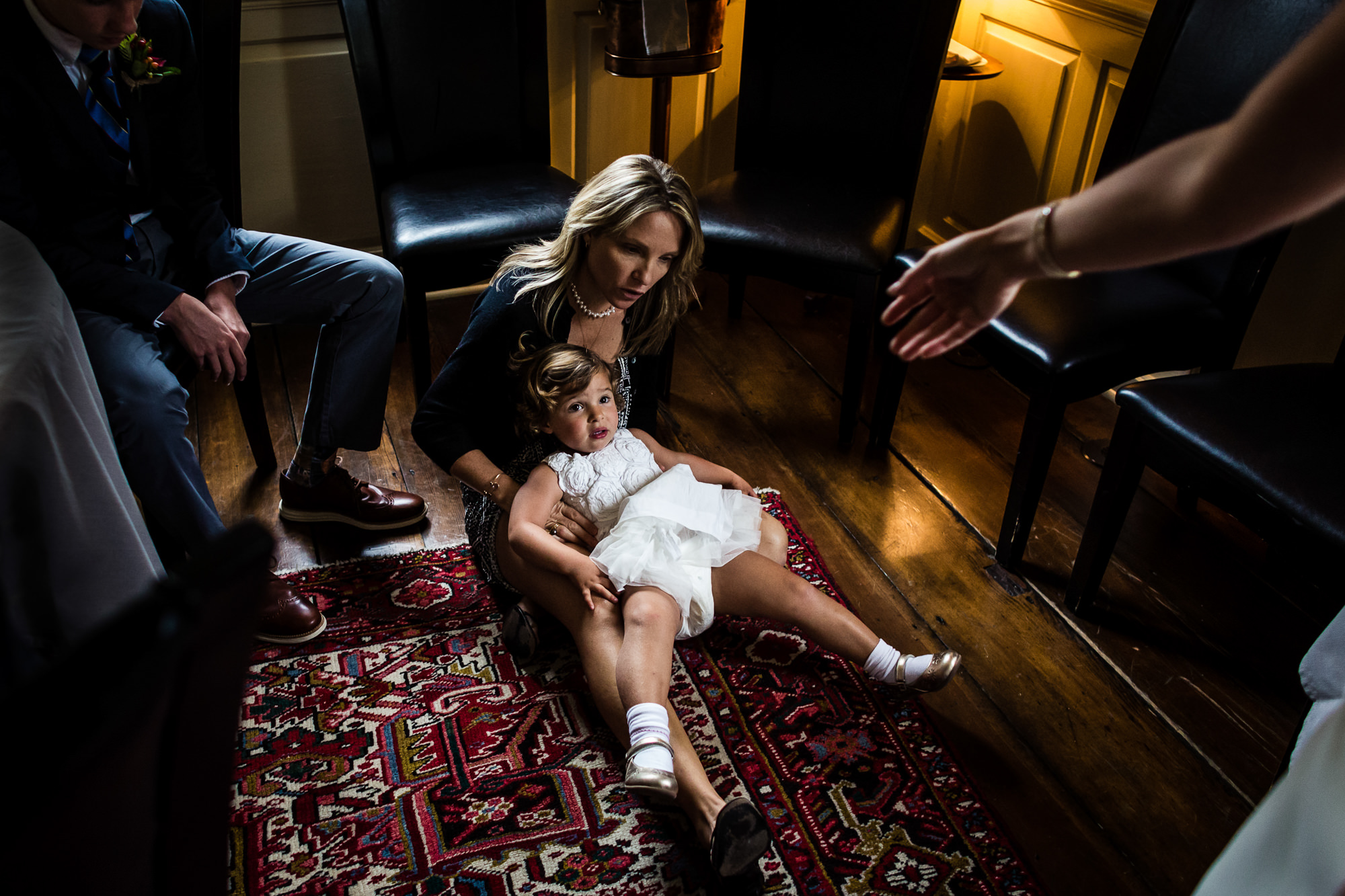 adorable-little-girl-sitting-on-moms-lap-with-hand-outstretched-worlds-best-wedding-photos-JAG-studios-connecticut-wedding-photographers