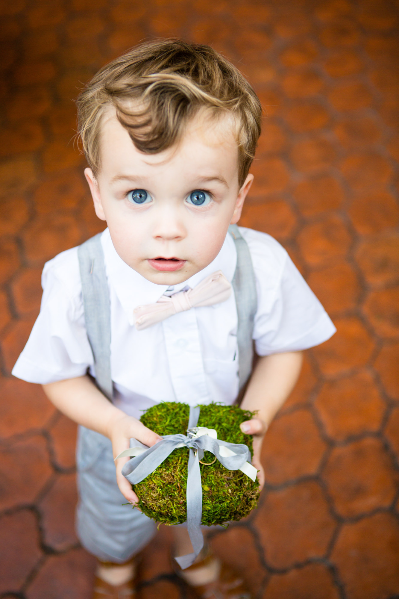 Ring bearer wearing shorts, suspenders, and pink bow tie - photo by La Vie Photo - San Juan Island