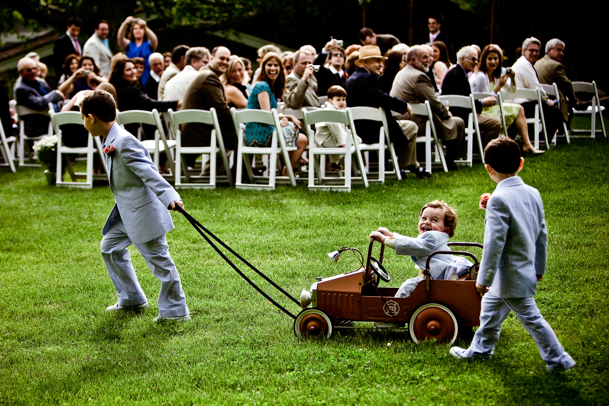 Ringbearers wearing blue seersucker suits pull toddler in toy car to ceremony - photo by Jag Studios