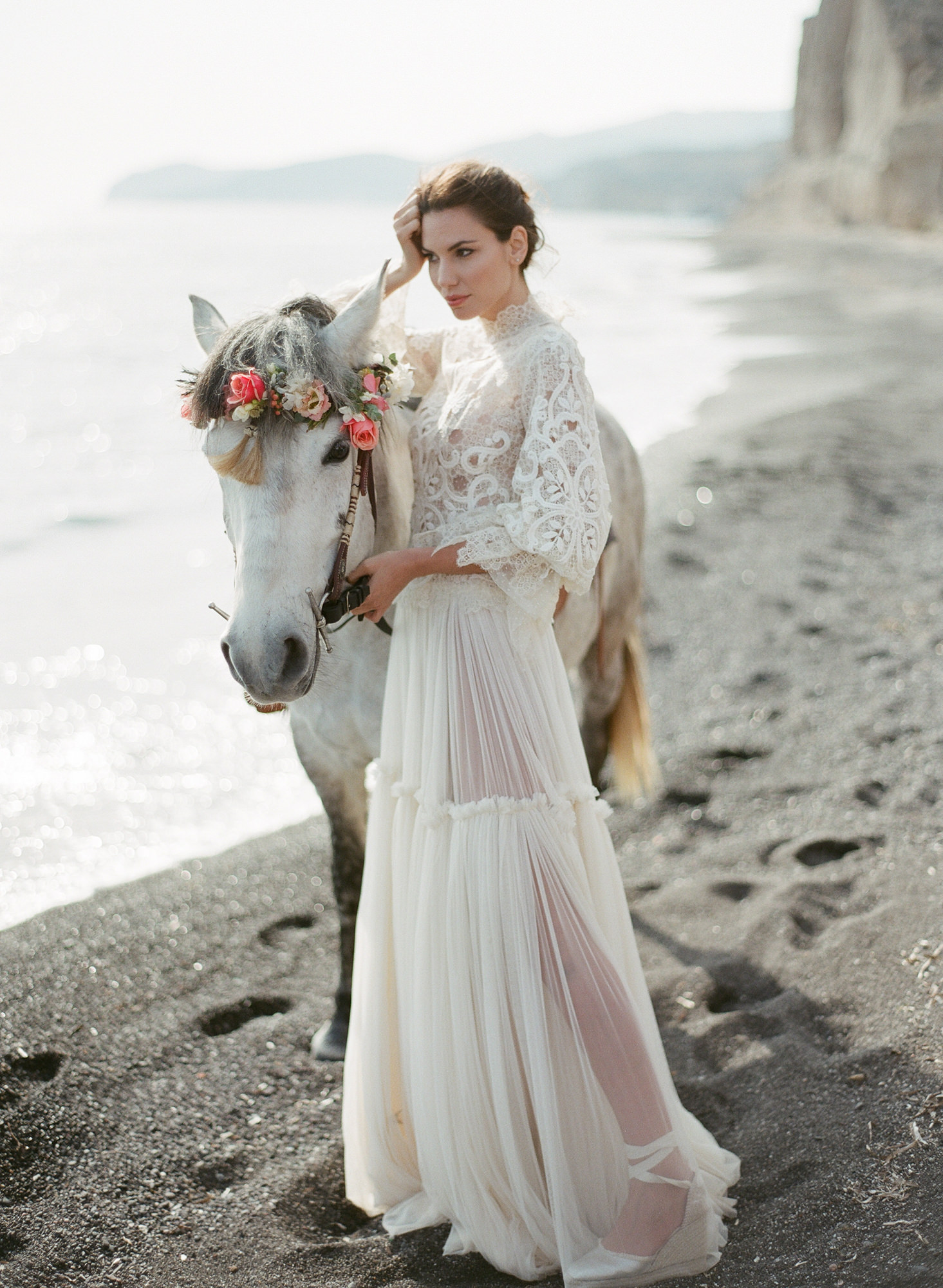 Bride on beach with vintage lace high neck gown - photo by Gianluca Adovasio