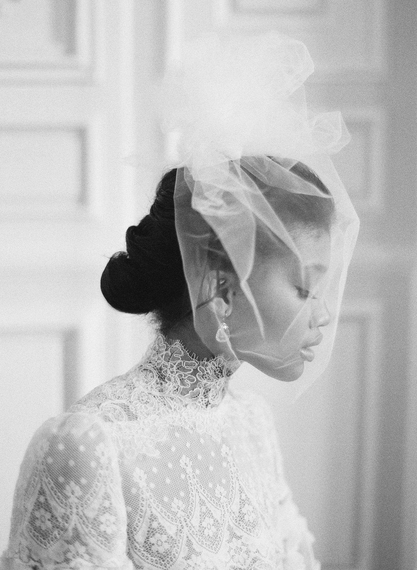 Bride wearing modest high neck gown with bird cage veil - photo by Greg Finck