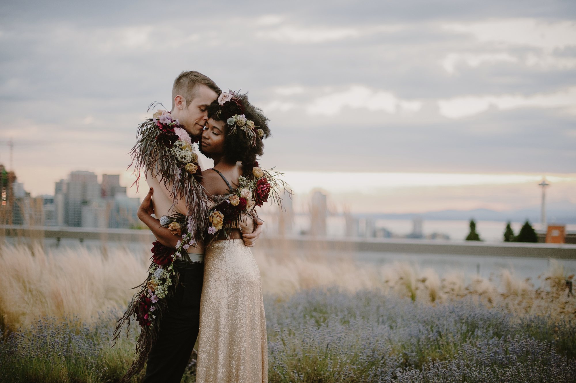Bride wearing golden skirt and bra top with long rustic floral garland - photo by Kristen Marie Parker - Seattle
