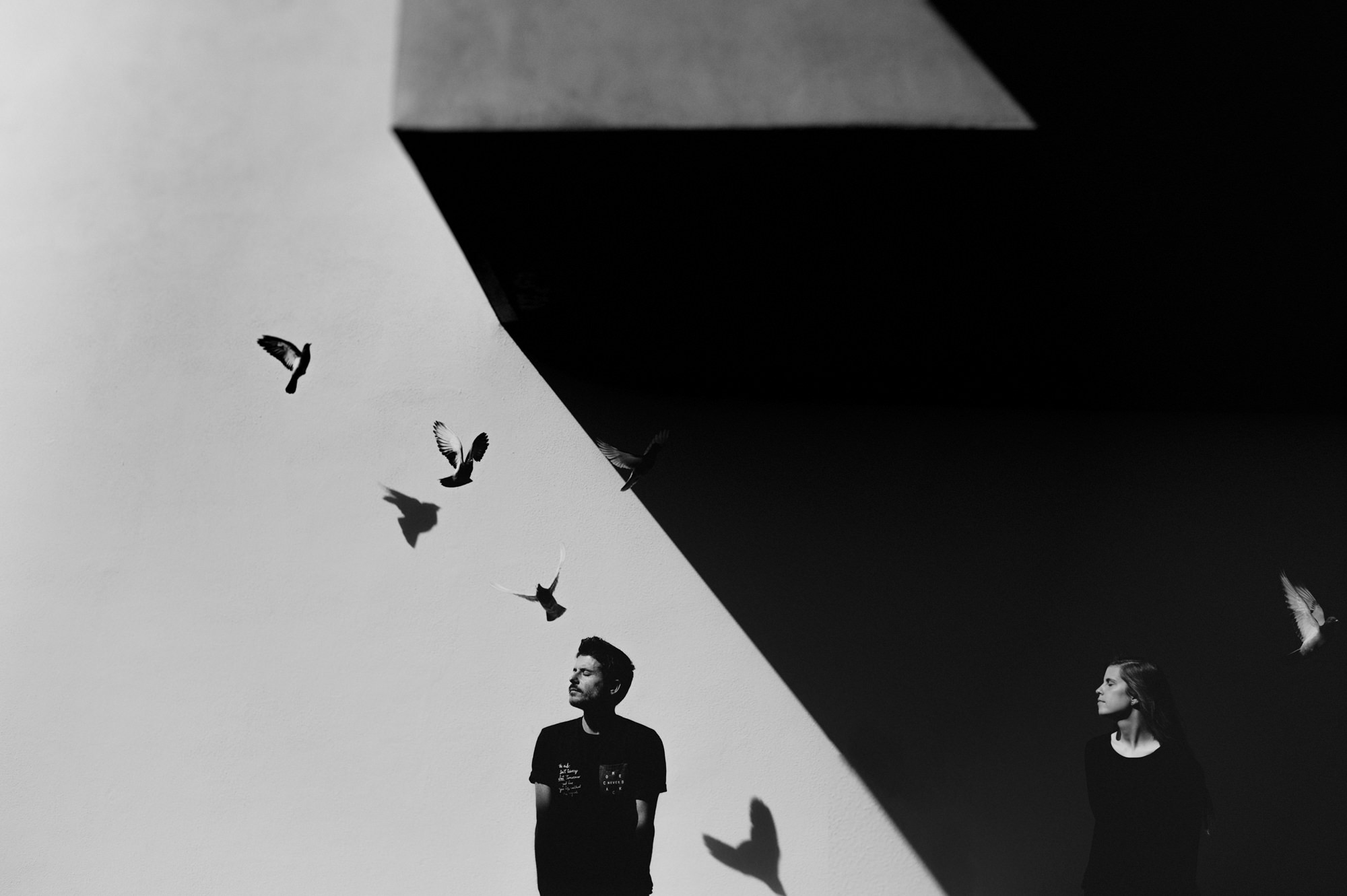 black-and-white-engagement-portrait-in-high-contrast-lighting-against-wall-with-birds-flying-worlds-best-wedding-photos-fer-juaristi-mexico-wedding-photographers