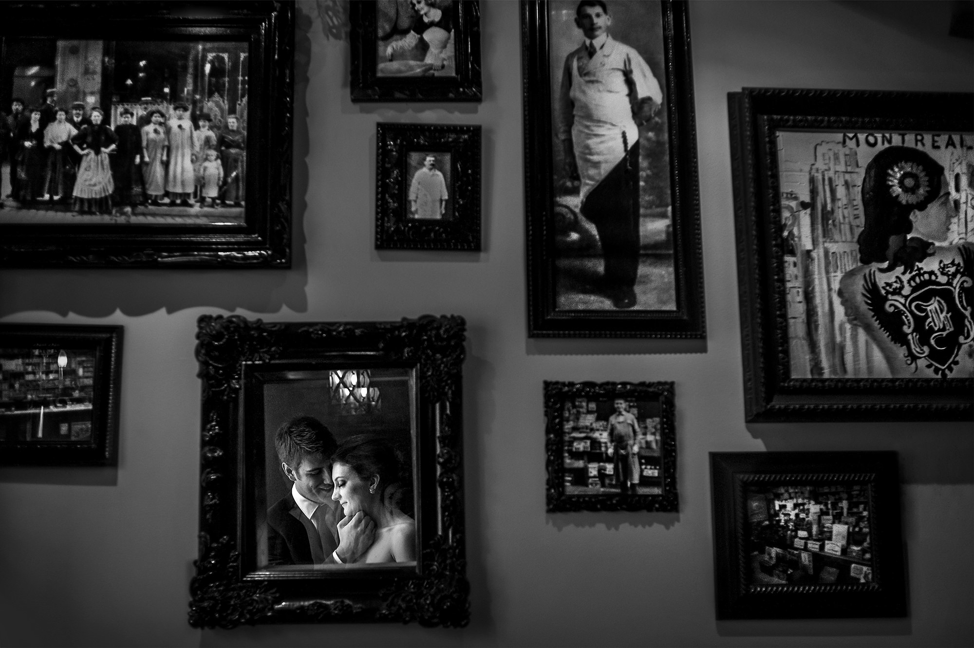 Couple reflected in mirror on wall of pictures - photographed by David and Sherry - Canada