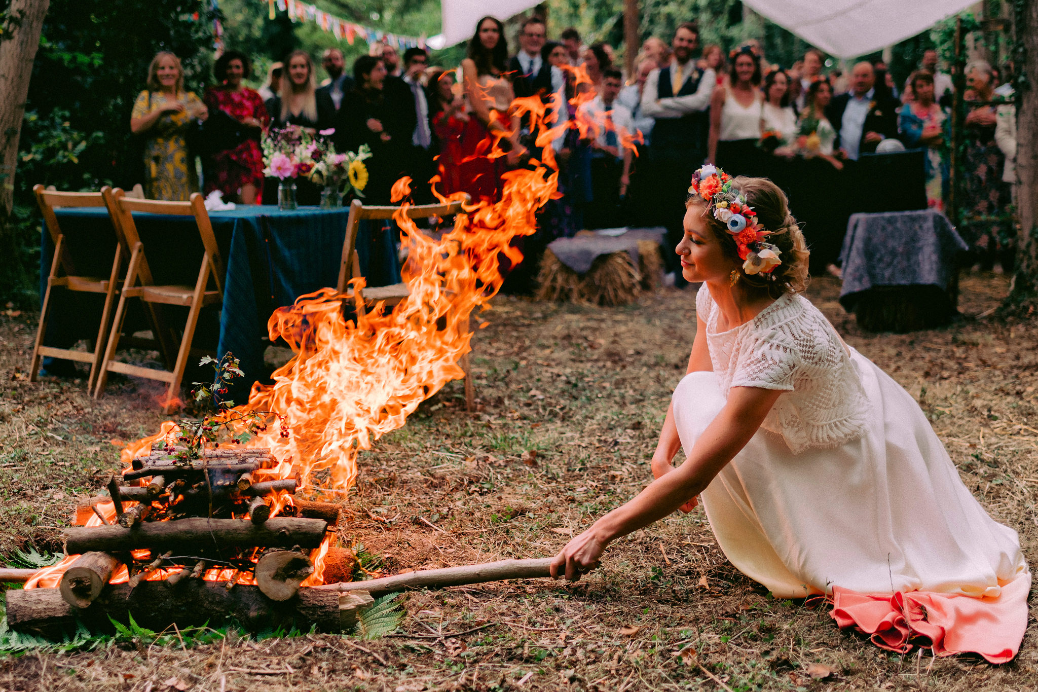 Bride in lace gown with floral crown stoking campfire - photo by Rich Howman - England