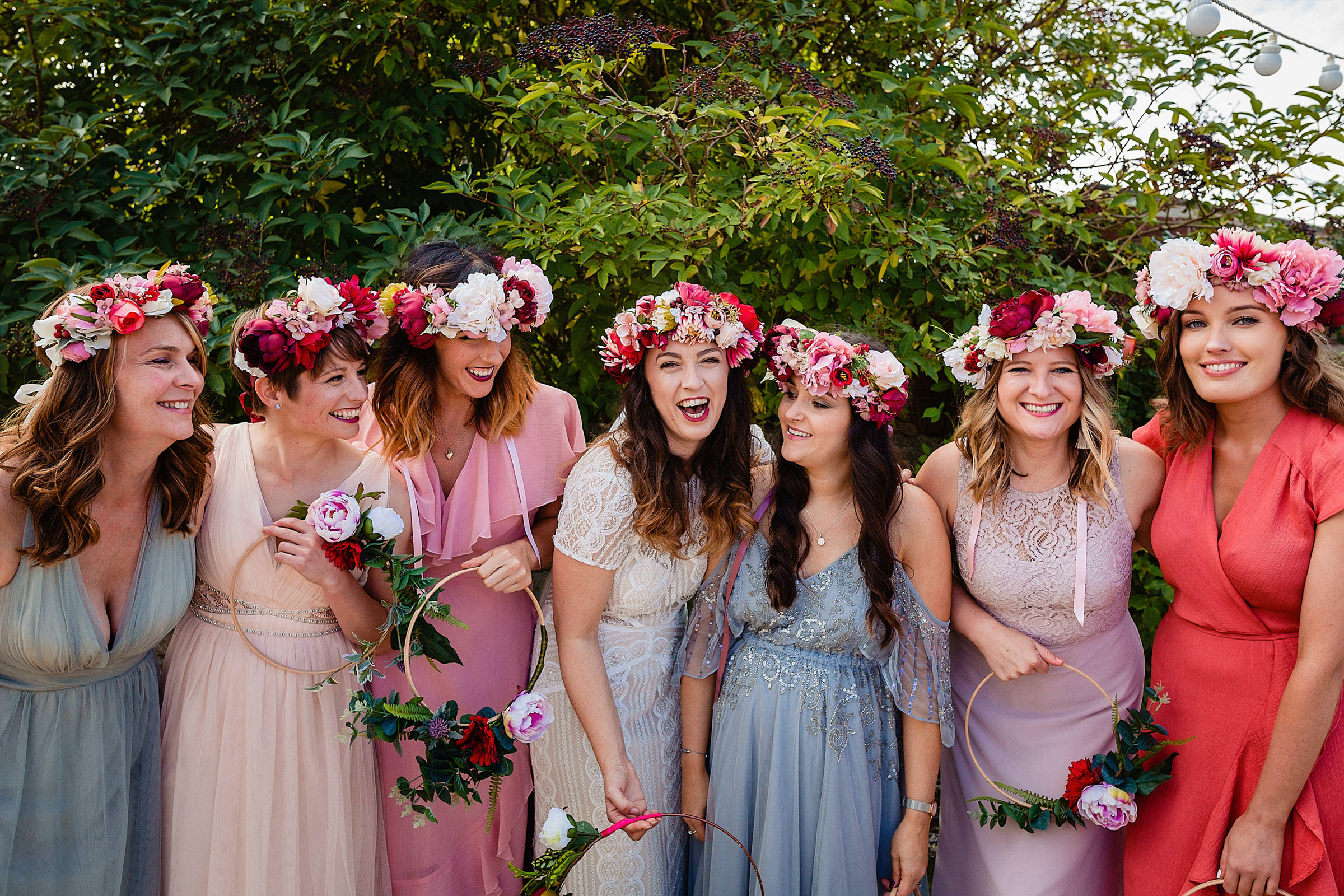 Bride and bridesmaids wearing floral crowns of pink and white peonies and roses photographed by Emma and Rich - UK photographers