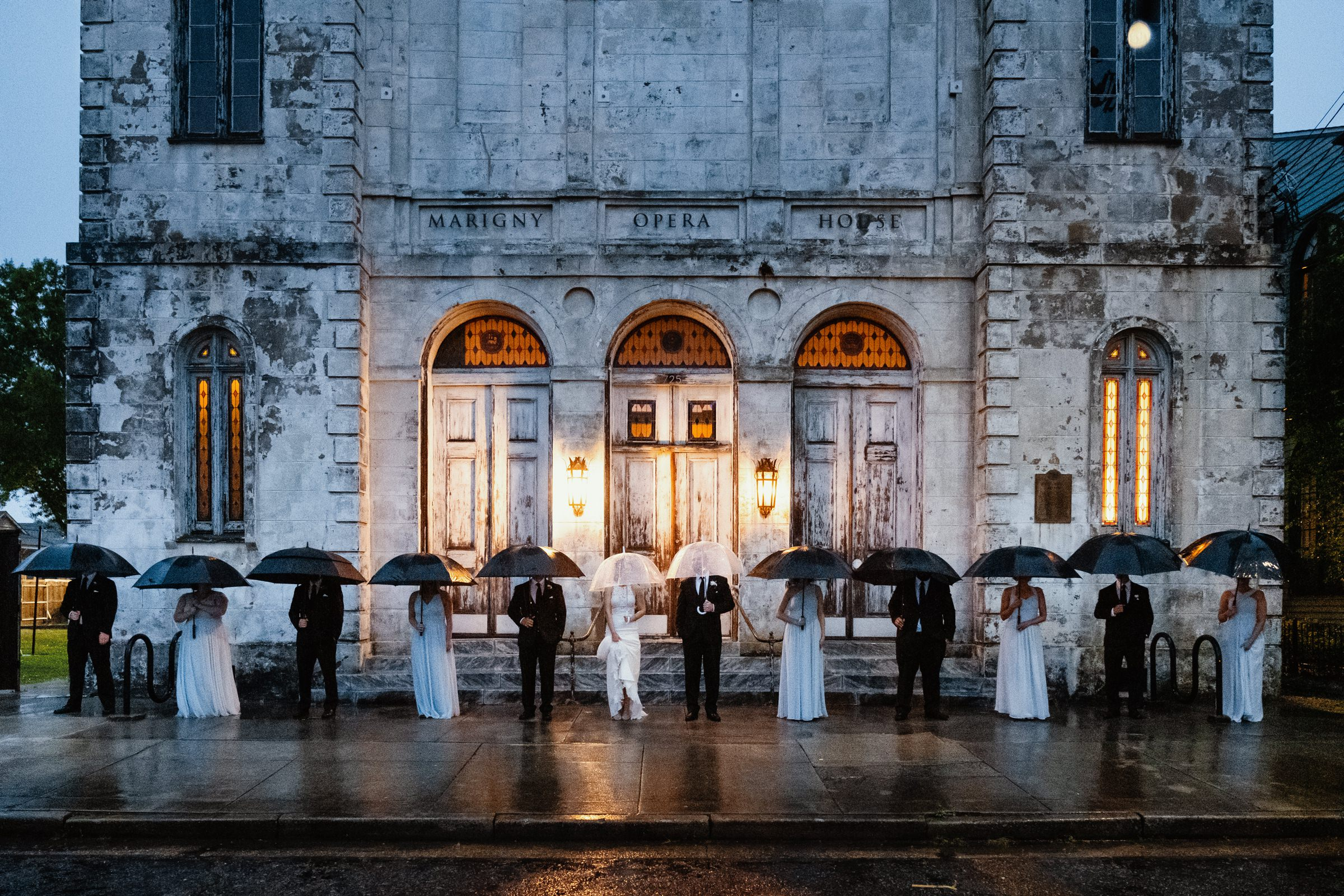 bridal-party-photo-in-the-rain-with-umbrellas-outside-venue-new-orleans-austin-houston-photo-by-dark-roux
