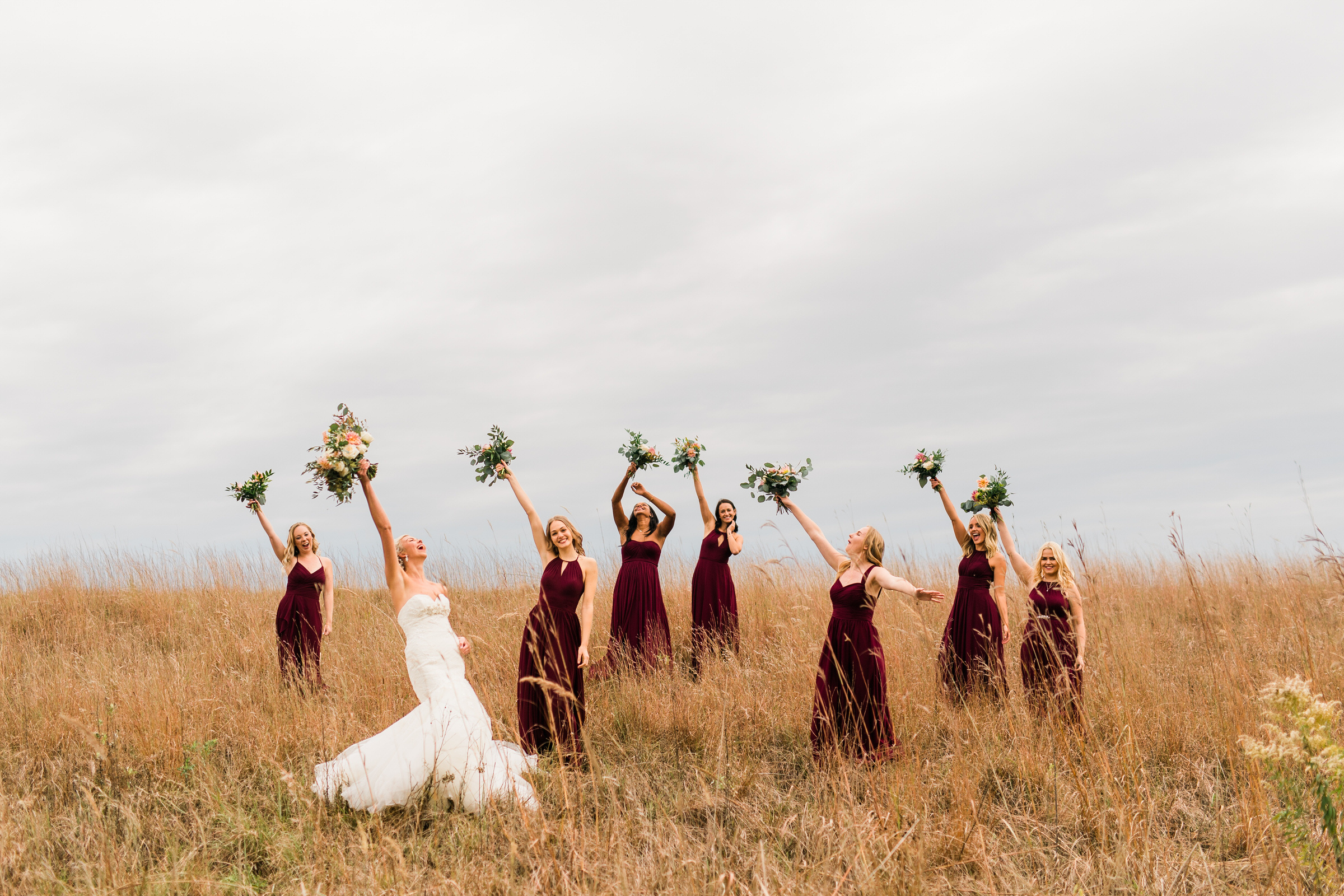 Bridesmaids in burgundy sleeveless gowns in grass field - photographed by M an J Studios - Estonia