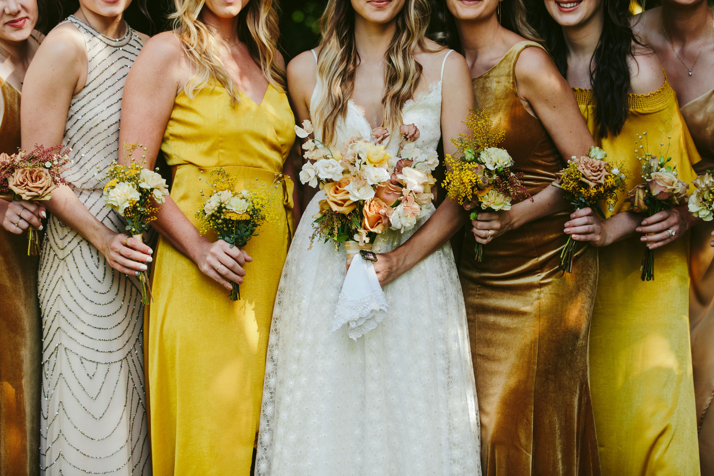 Bridal party with bouquets wearing silk bronze, yellow, and ivory dresses - photographed by Melia Lucida - Maui