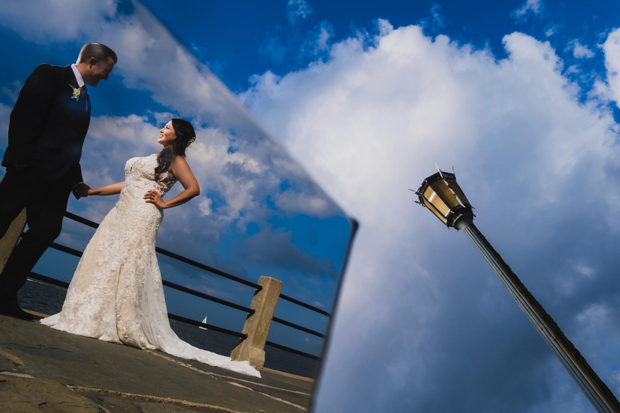 Bride and groom reflected against mirror under streetlight - photo by Chrisman Studios - Charleston