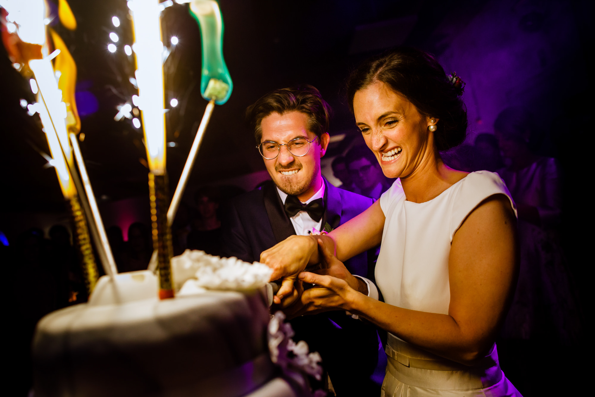 bride-and-groom-cut-cake-with-a-vengeance-worlds-best-wedding-photographers-philippe-swiggers