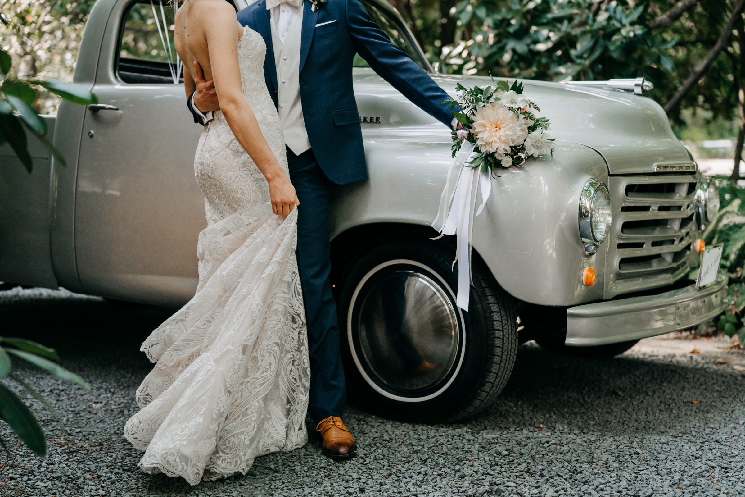 Bride and groom embrace against silver vintage Studebaker truck - photo by Sasha Reiko