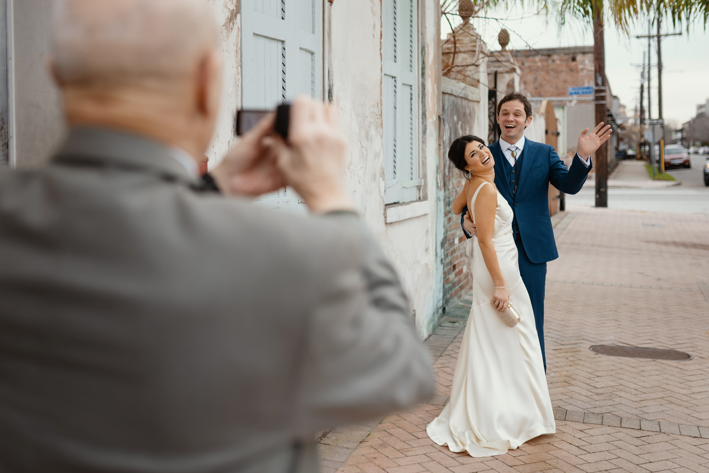 bride-and-groom-having-photo-taken-of-them-by-guest-new-orleans-austin-houston-photo-by-dark-roux