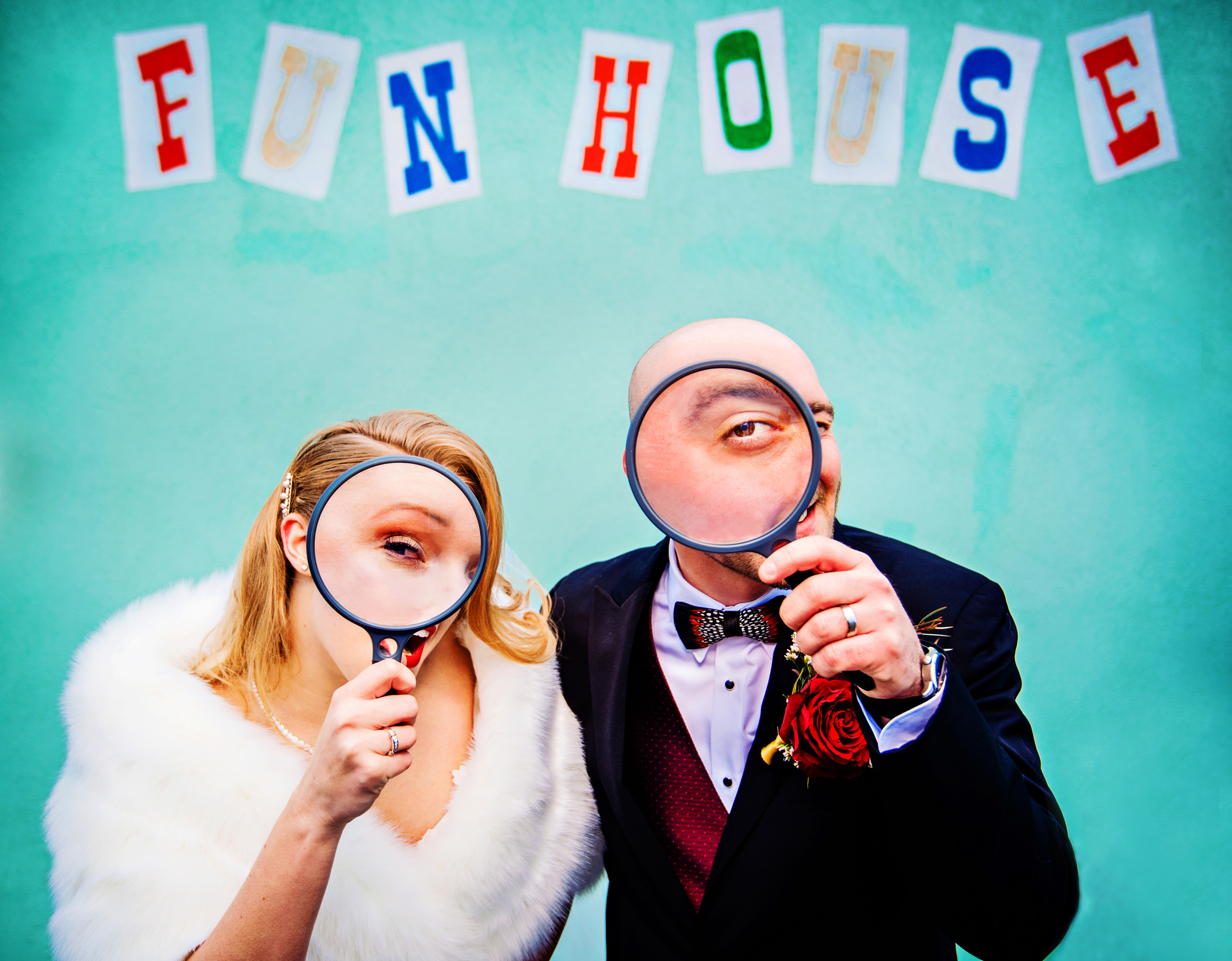 bride-and-groom-look-through-magnifying-glasses-under-fun-house-sign-jeff-tisman-photography-new-york