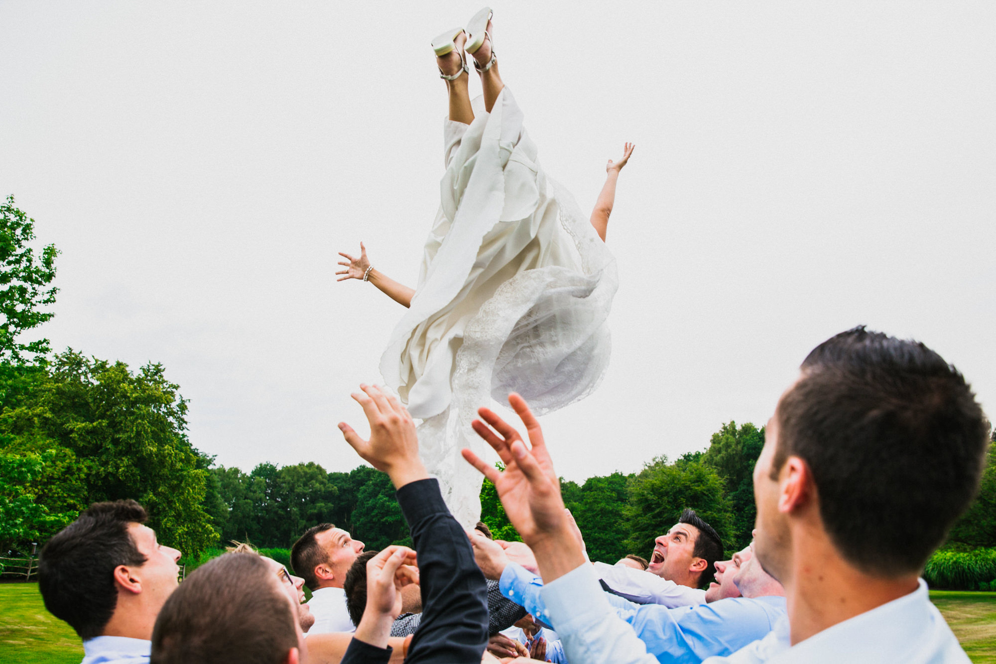 Bride gets tossed feet first in the air by groosmen - photo by Philippe Swiggers