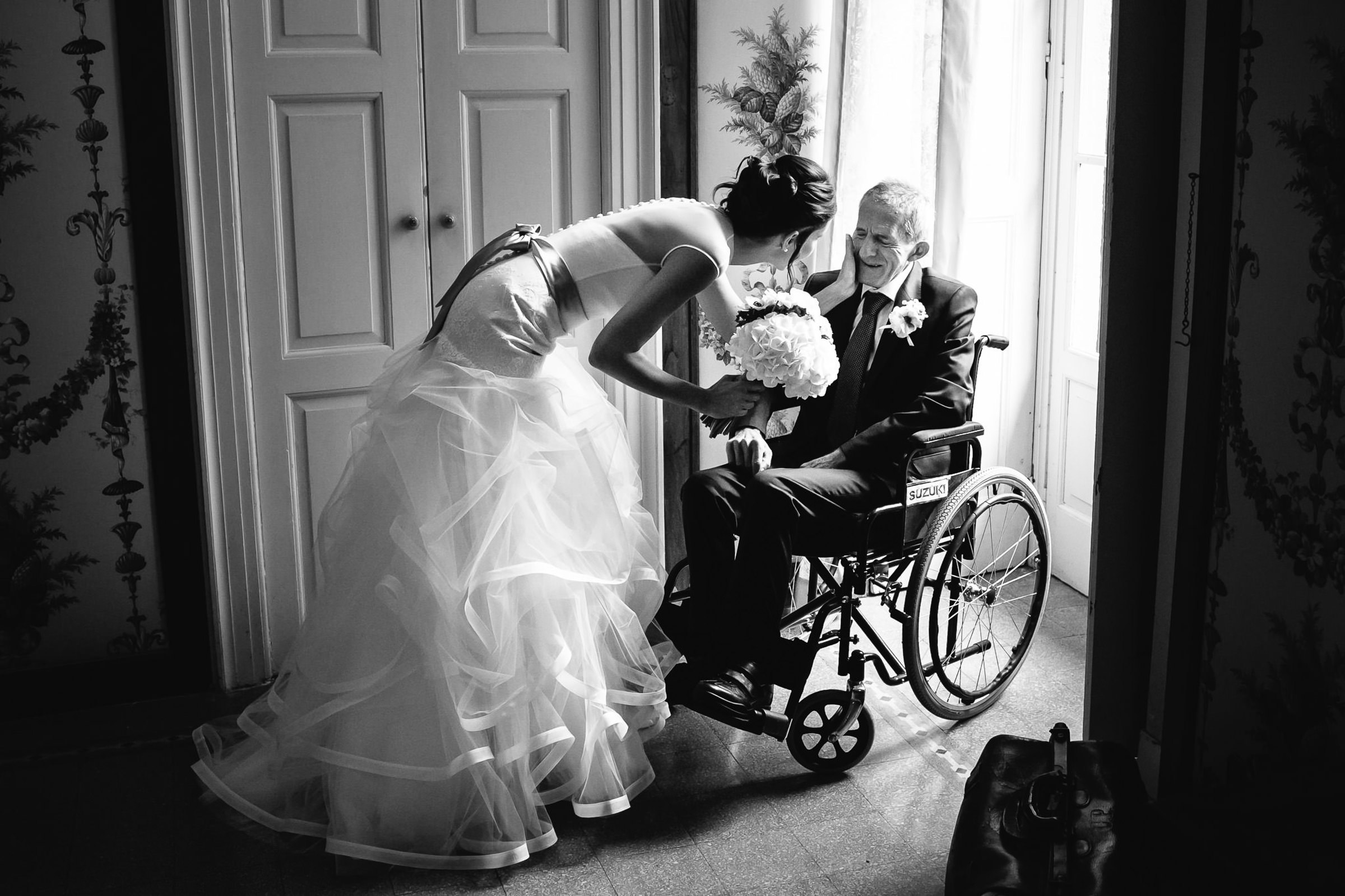 Bride bends down to touch her grandfather's face - Julian Kanz - Italy