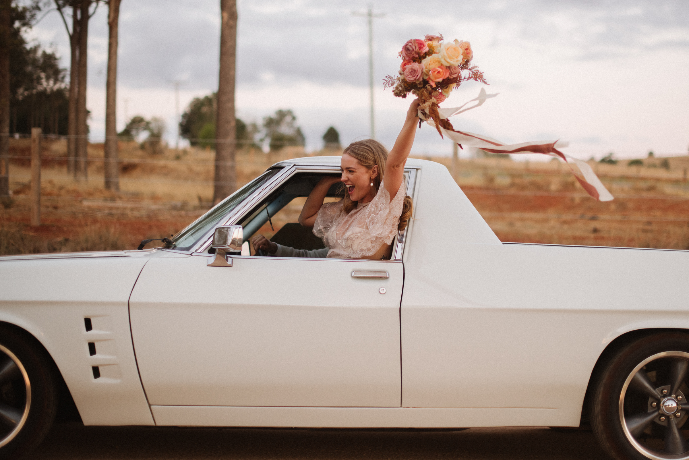 bride-excited-while-driving-away-from-ceremony-with-bouquet-out-window-ben-sowry-photo-australia