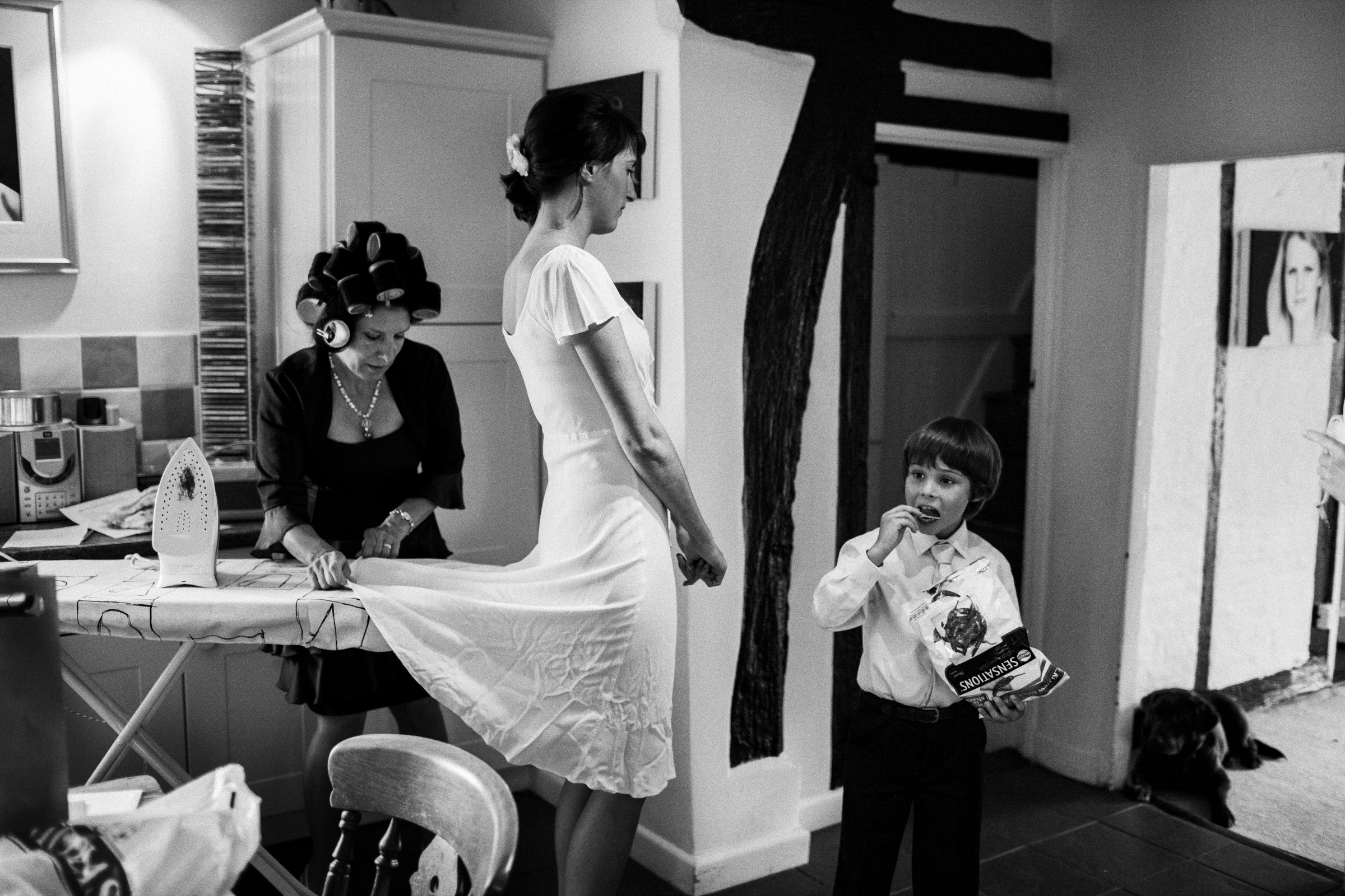 Mother irons brides dress while she wears it - documentary photo by Jeff Ascough, London