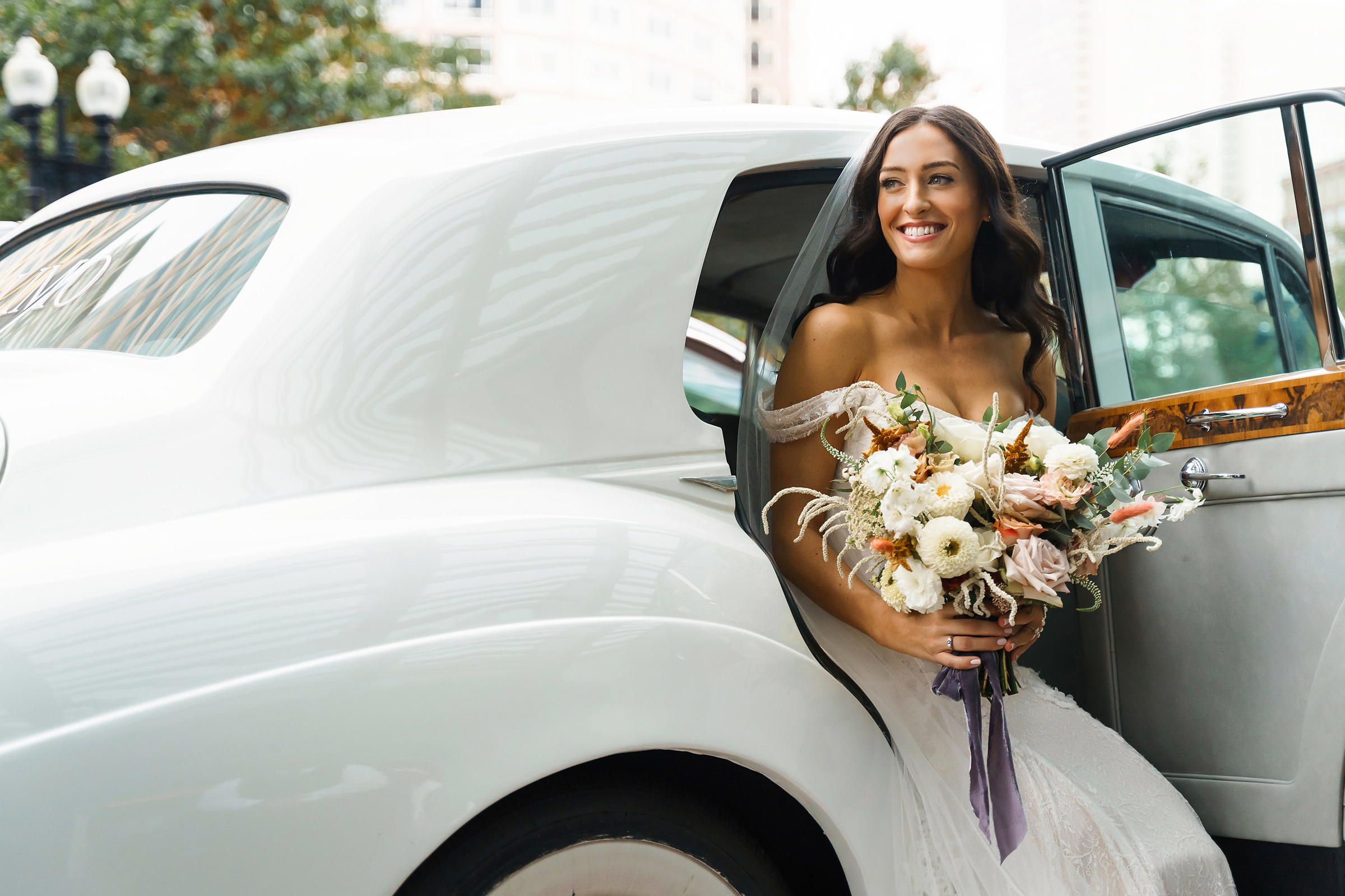 Bride getting out of white limo by Alex Gordias - Cape Cod, MA