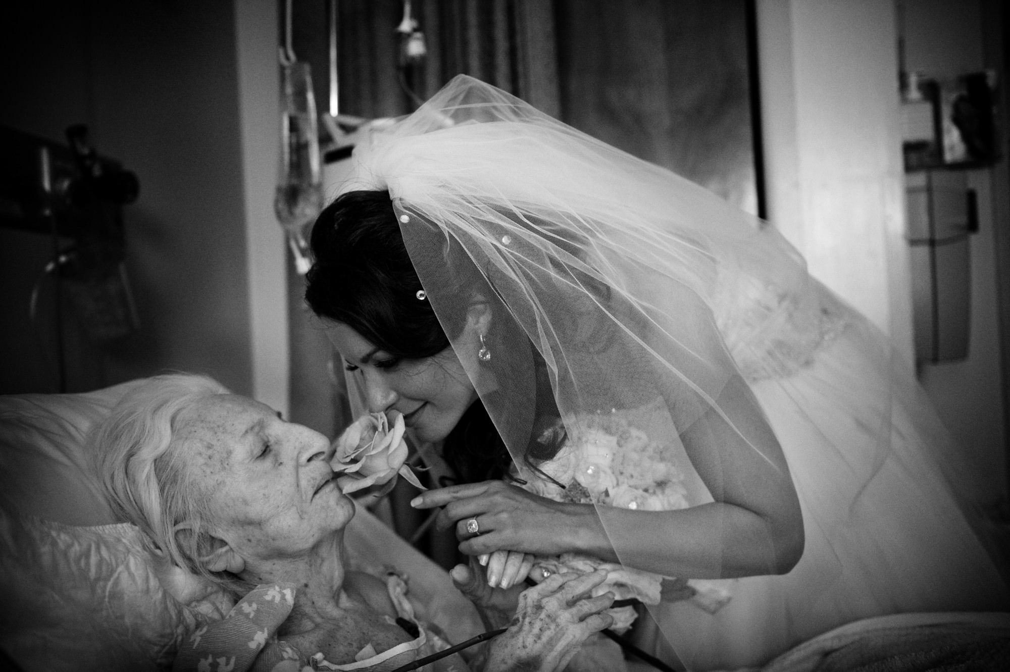 Bride leans down to kiss her ailing grandmother - photo by Cliff Mautner - New York